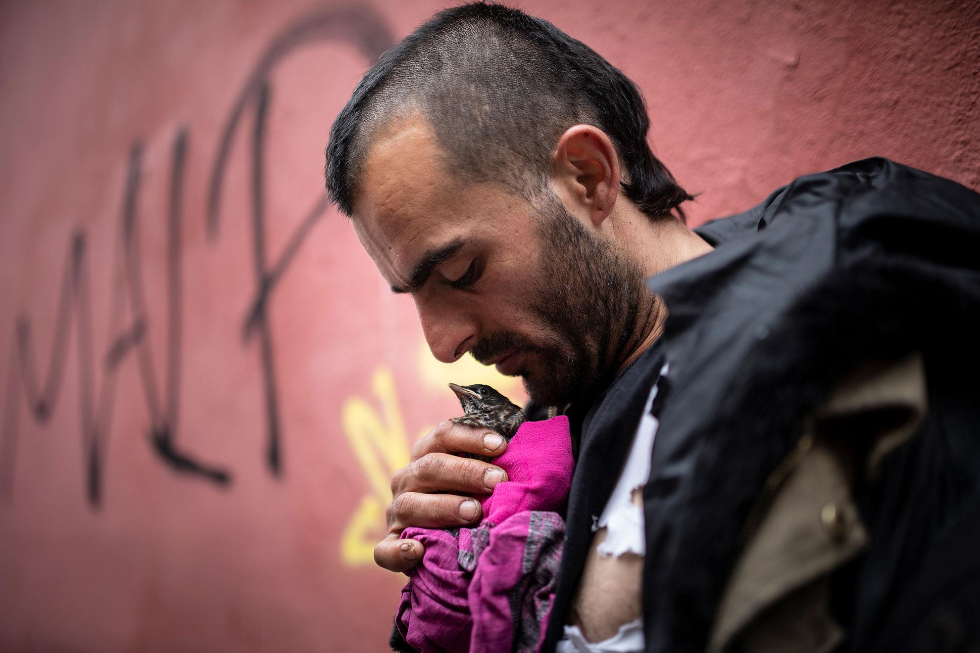 Luis (35) es de Coímbra. Llegó hace año y medio a Madrid, y está viviendo en la calle. Es artista callejero: realiza decoraciones, customiza ropa e incluso trabaja en raves. Cuando no sale nada de eso, hace malabares en los semáforos para subsistir. Ha encontrado un pájaro herido y se afana en cuidarlo durante estos días raros, en los que todos estamos algo necesitados de afectos. Duerme al raso, en el barrio de Lavapiés, y en la asociación Los Dragones le dan comida a diario, ahora que es casi imposible ganarse la vida en la calle, porque apenas hay vida en las calles a causa del Covid-19.