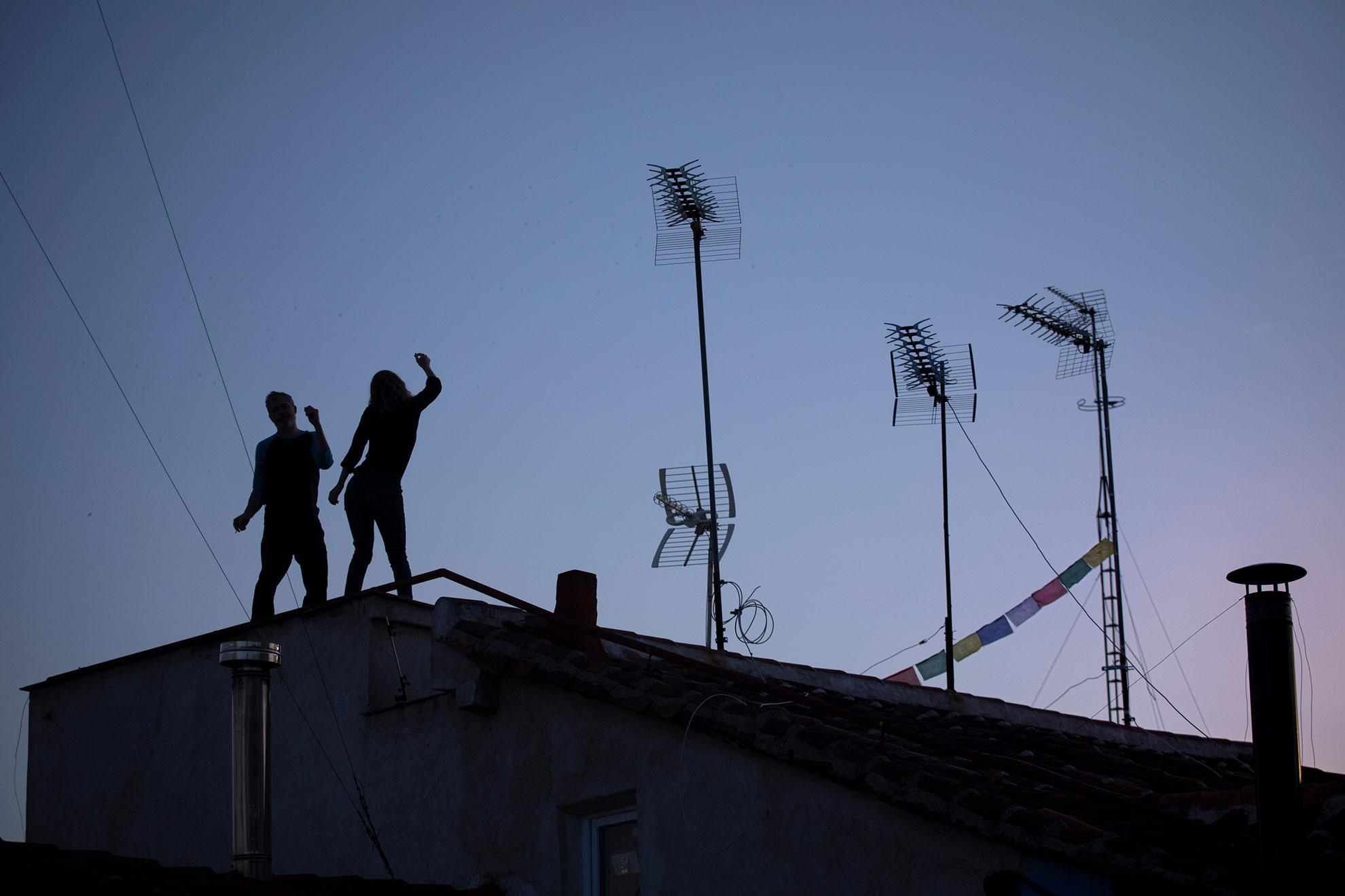 """Bailando sobre los tejados, al son de Joaquín Sabina, los vecinos de Lavapiés escapan del confinamiento durante unos minutos. Todos los domingos, después de los aplausos de las ocho, Gabriel saca la guitarra a su balcón de la calle del Olmo y toca un par de canciones. Los vecinos ya lo saben, y esperan a que empiece el concierto. Ayer interpretó """"Pongamos que hablo de Madrid"""", esa ciudad donde las niñas ya no quieren ser princesas, prefieren subir al tejado y bailar, esperando que el distanciamiento social que ha impuesto el Covid-19 acabe de una vez y la vida vuelva a inundar las calles. ."""