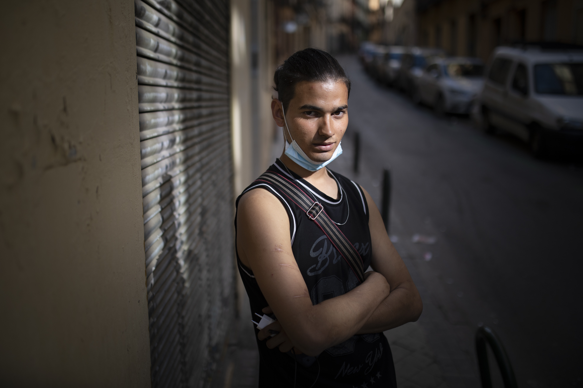 """Younes Baiz (20) llegó a España en la bodega de un barco procedente de Tánger, viajaba como polizón. Fue en 2014, y por aquel entonces era menor de edad. A su llegada a Cádiz, la policía lo descubrió y lo trasladó a un CIE. Cuando cumplió 18 encontró trabajo en un asador de pollos y arregló sus papeles. """"Tenía dinero en el banco, vestía bien, vivía bien"""", cuenta. Pero decidió mudarse a Madrid el verano pasado, y aquí no consiguió nada. Ahora está en la calle. Todos los días camina desde el barrio del Pozo hasta Lavapiés para recoger la comida que le dan en el Teatro del Barrio (ahora reconvertido en banco de alimentos). Younes sólo espera a que levanten las restricciones a causa del Covid-19 para irse de esta ciudad. """"A un sitio con campo, para poder trabajar la tierra, ganar dinero y volver a Marruecos con la cabeza alta"""", dice."""