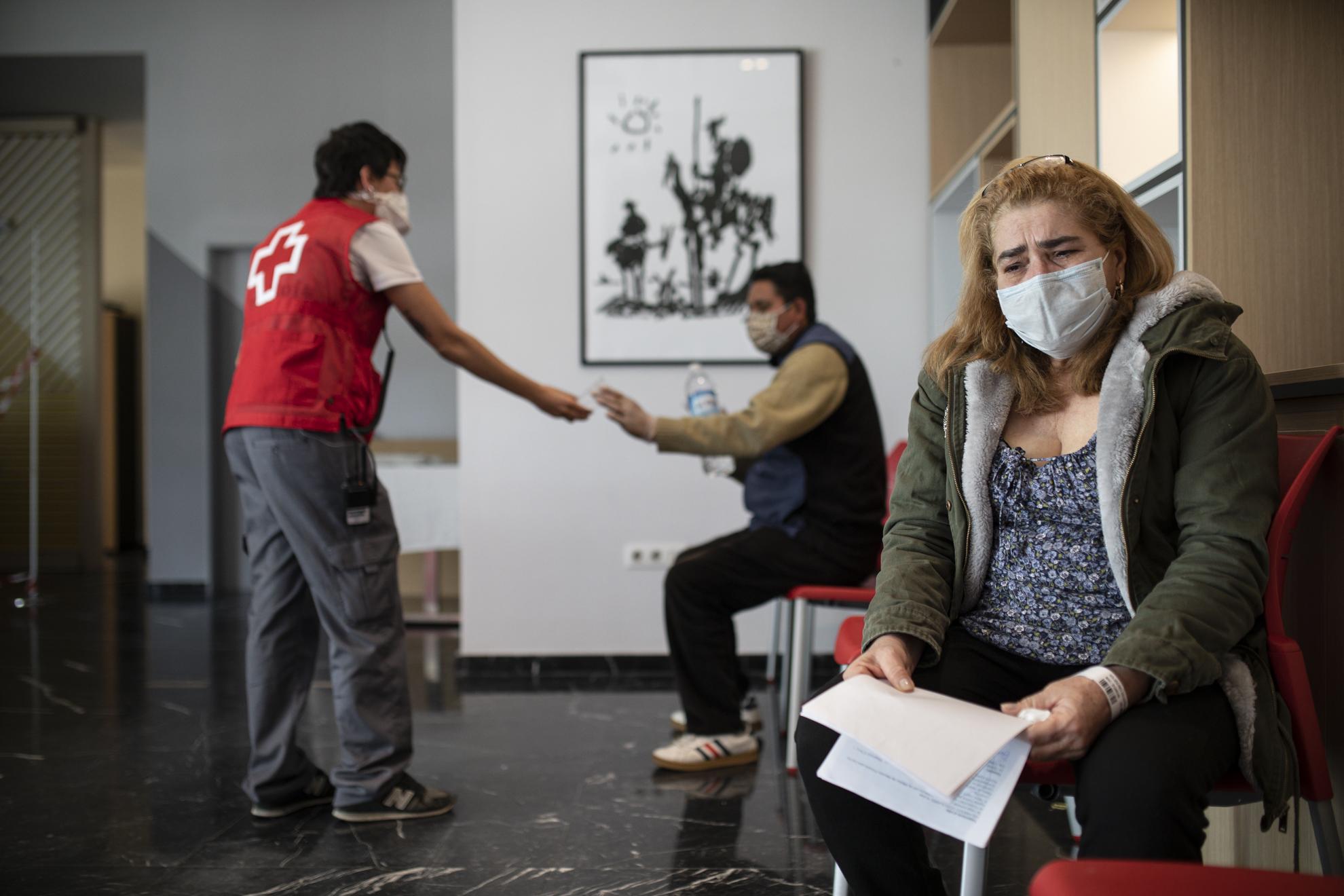 """Rosalía (64) es refugiada. Vino de Honduras hace dos años y estudió peluquería. En un mes, han fallecido tres de sus hermanos. No han podido velarles, a pesar de que uno de ellos murió a causa de un problema cardíaco que no tenía nada que ver con el Covid-19. Perdió su trabajo justo después, y sus ingresos, y no pudo pagar la habitación que tenía alquilada en Madrid. Se ha quedado en la calle, obligada a guardar cuarentena, porque las personas con las que compartía piso tuvieron coronavirus. Cruz Roja la ha llevado al hotel Holiday Inn las Tablas, ahora medicalizado, donde alojan temporalmente a personas como Rosalía. """"Por mi edad, todo me lo ponen difícil. Me llaman para entrevistas de trabajo, pero cuando les digo mi edad ya no les intereso"""", se lamenta. Sueña con volver a ver a sus hijos, y a su nieto, cuando se restablezca. Ellos desconocen las penurias por las que está pasando Rosalía en España."""