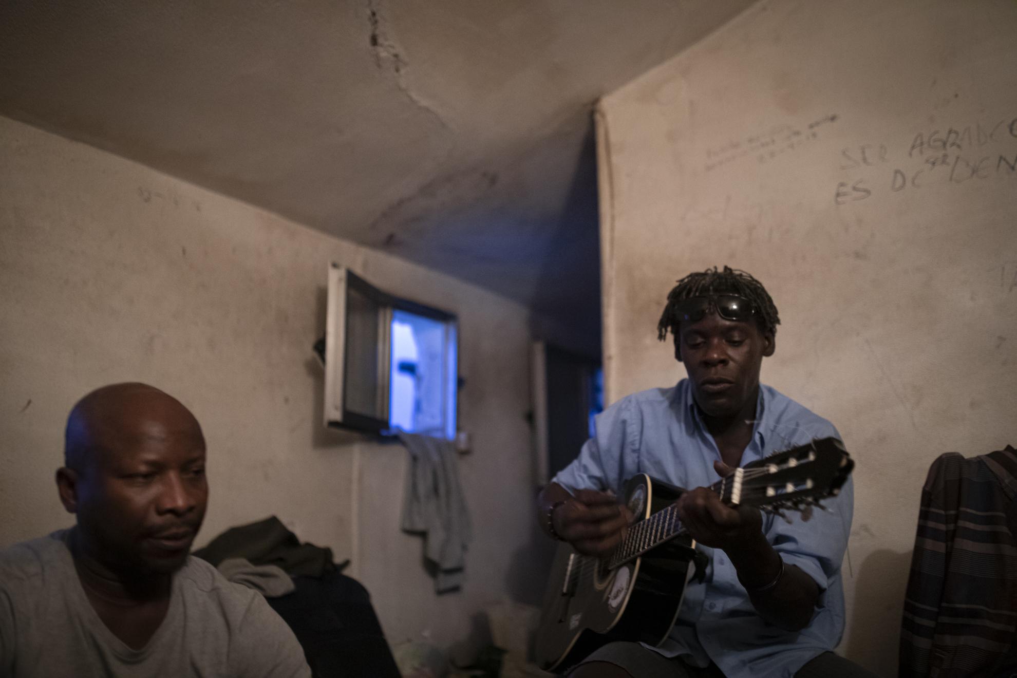 Yusuf (izquierda) y Bruno (con su guitarra entre las manos) continúan viviendo como pueden esta crisis sanitaria. Siguen sin agua corriente en su pequeño piso de Lavapiés, pero desde que se han atenuado las restricciones para salir a la calle lo llevan mejor. Ahora que hay más vida, y mucha más gente por el barrio, tienen también más facilidades para conseguir comida. Bruno tiene un trabajo a la vista, en Alicante, donde está pensando mudarse cuando se pueda viajar a otras provincias. Ninguno de los dos habla con su familia en Guinea; no quieren preocuparles con las noticias sobre el Covid-19 que siguen sonando con pesadumbre en los medios de comunicación en España.