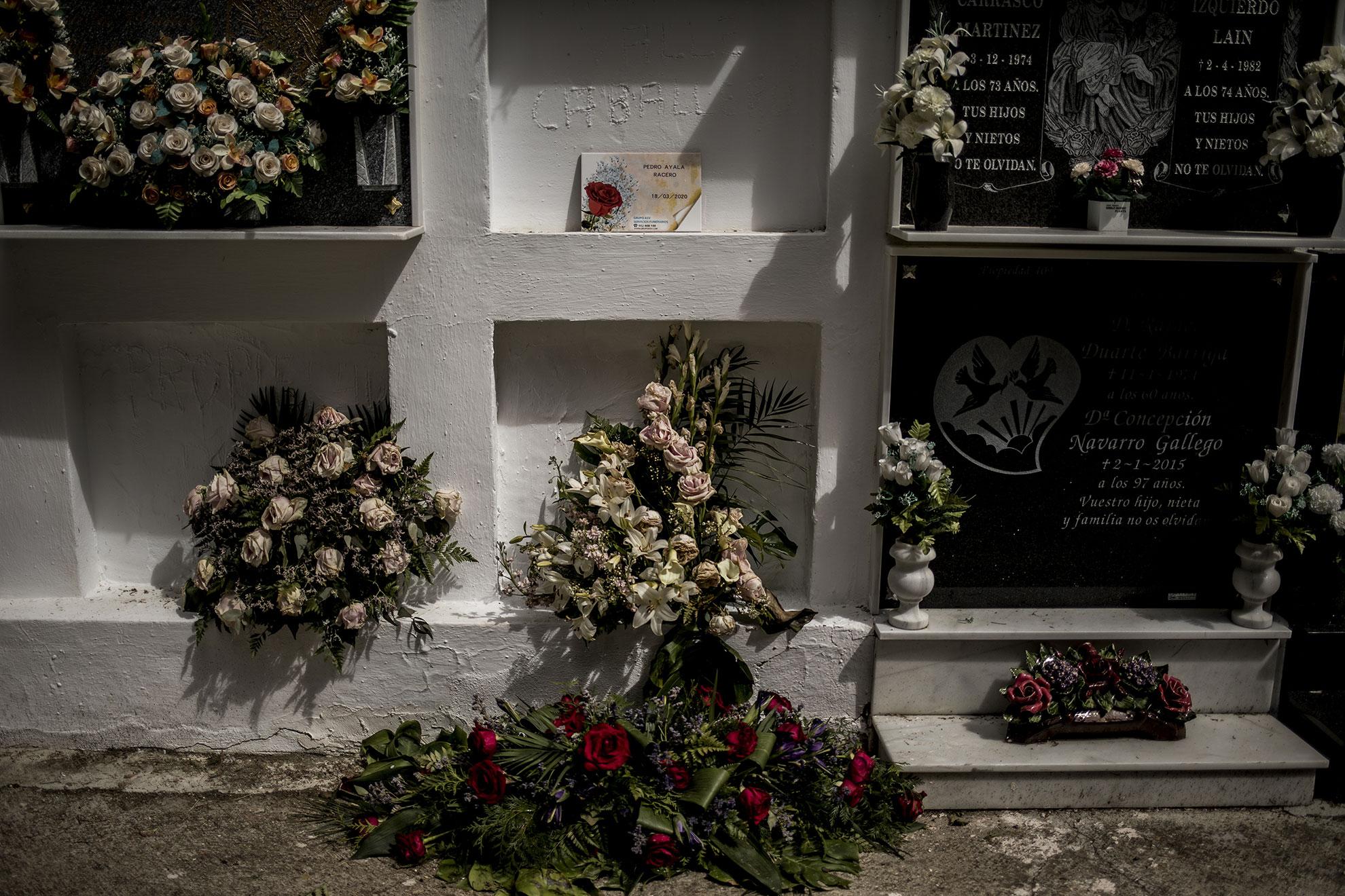 Ramos de flores languidecen junto al nicho de un fallecido en el cementerio de Alcalá del Valle, donde un contagio masivo en la residencia de ancianos se cobró la vida de seis personas y otras 58 fueron contagiadas por COVID-19. En el pueblo se suceden las protestas para que la administración realice tests a los vecinos, que viven atemorizados.