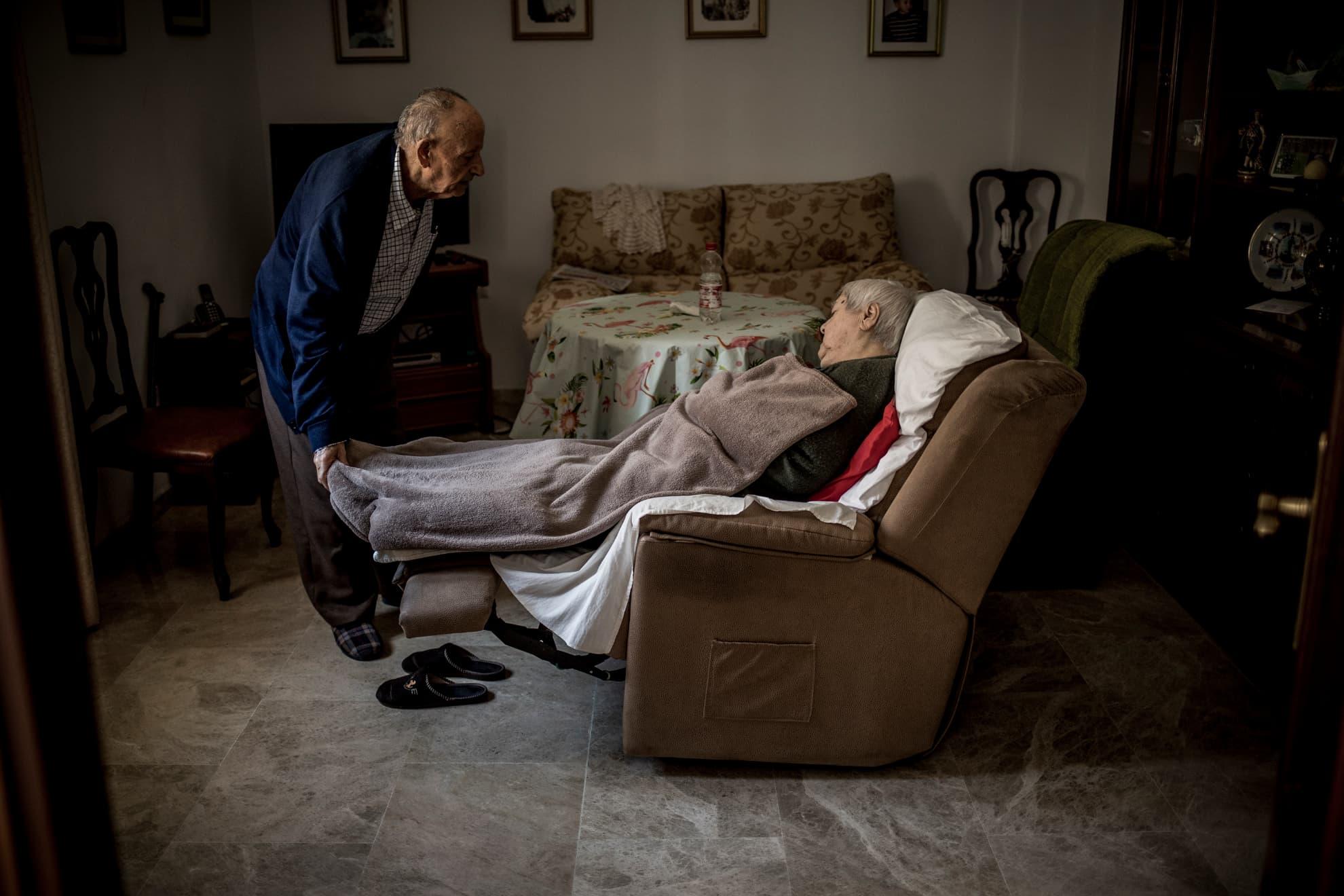 Manuel Ramos y Josefa Contreras comparten vida y edad, ambos tienen 86 años. Hace diez años, Josefa fue diagnosticada con DCL (Demencia con Cuerpos de Lewy), una enfermedad degenerativa del cerebro cuyos síntomas se asemejan al Alzheimer. Ninguno de los dos ha salido de casa desde el comienzo del estado de alarma. Manuel solía ir a un bar cercano a leer el periódico durante una hora cada día, mientras una persona del servicio de asistencia a domicilio cuidaba de Josefa. Hoy en día no puede hacerlo por las restricciones impuestas por la pandemia y porque esa ayuda diaria se ha reducido a dos días a la semana, al estar en servicios mínimos. En Jerez, Cádiz, el 29 de abril de 2020.