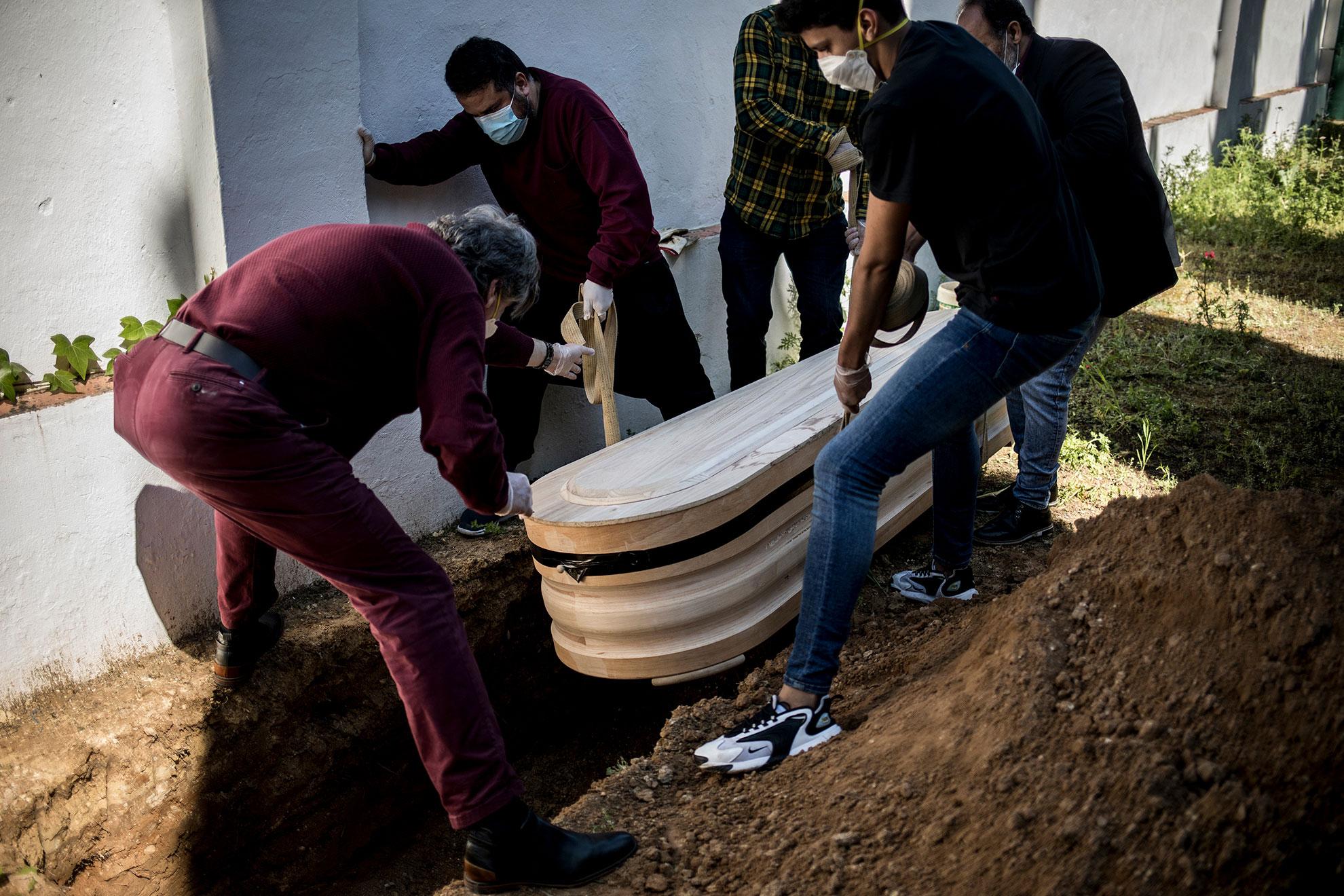 Trabajadores de la empresa funeraria y allegados introducen el ataúd sellado de una persona fallecida a causa de complicaciones por la infección del virus COVID-19 en su tumba. El fallecido, un varón de 77 años de origen marroquí, falleció en el hospital de Algeciras pero ha sido enterrado en el cementerio de Jerez, ya que dicho camposanto cuenta con un cementerio musulmán propio, el único en la provincia de Cádiz.