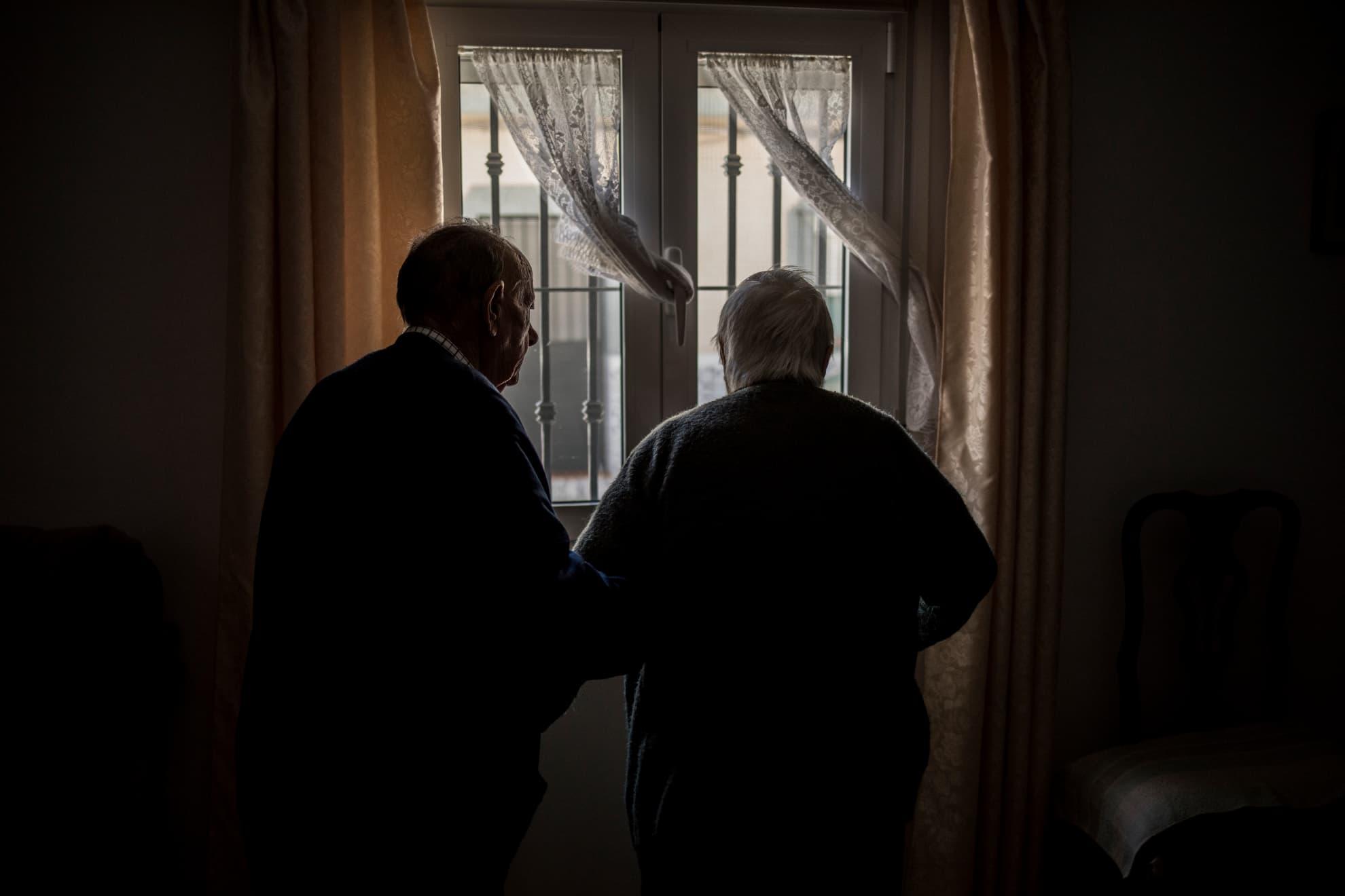 """Manuel despierta a Josefa del profundo sueño que le produce la medicación. Es hora de ir a lavarse las manos y sentarse a la mesa para comer, pero antes se acercan a la ventana a mirar la calle, desierta de vida, como si de un ritual diario se tratara. Josefa duerme la mayoría del día; """"son las pastillas"""" comenta Manuel. Hace diez años, fue diagnosticada con DCL: demencia con cuerpos de Lewy, una enfermedad degenerativa del cerebro cuyos síntomas se asemejan al Alzheimer. """"Hay días peores y días mejores"""", dice Manuel, """"Mi hijo propuso que la internásemos en una residencia, pero mientras yo pueda no voy a hacerle eso"""". Llevan más de 45 días sin salir a la calle a dar sus paseos por la pandemia por COVID-19. Manuel hace escasamente un mes que salió del hospital por problemas respiratorios graves, justo antes de que el coronavirus llegara para quedarse; Josefa no sabe qué ocurre, en algún momento lúcido parece entender que hay un virus que puede ser mortal para ellos, pero pronto lo olvida. Manuel dedica sus días a atender su esposa desde que el estado de alarma recortara la necesaria ayuda a domicilio, a servicios mínimos. En Jerez, Cádiz, el 29 de abril de 2020."""