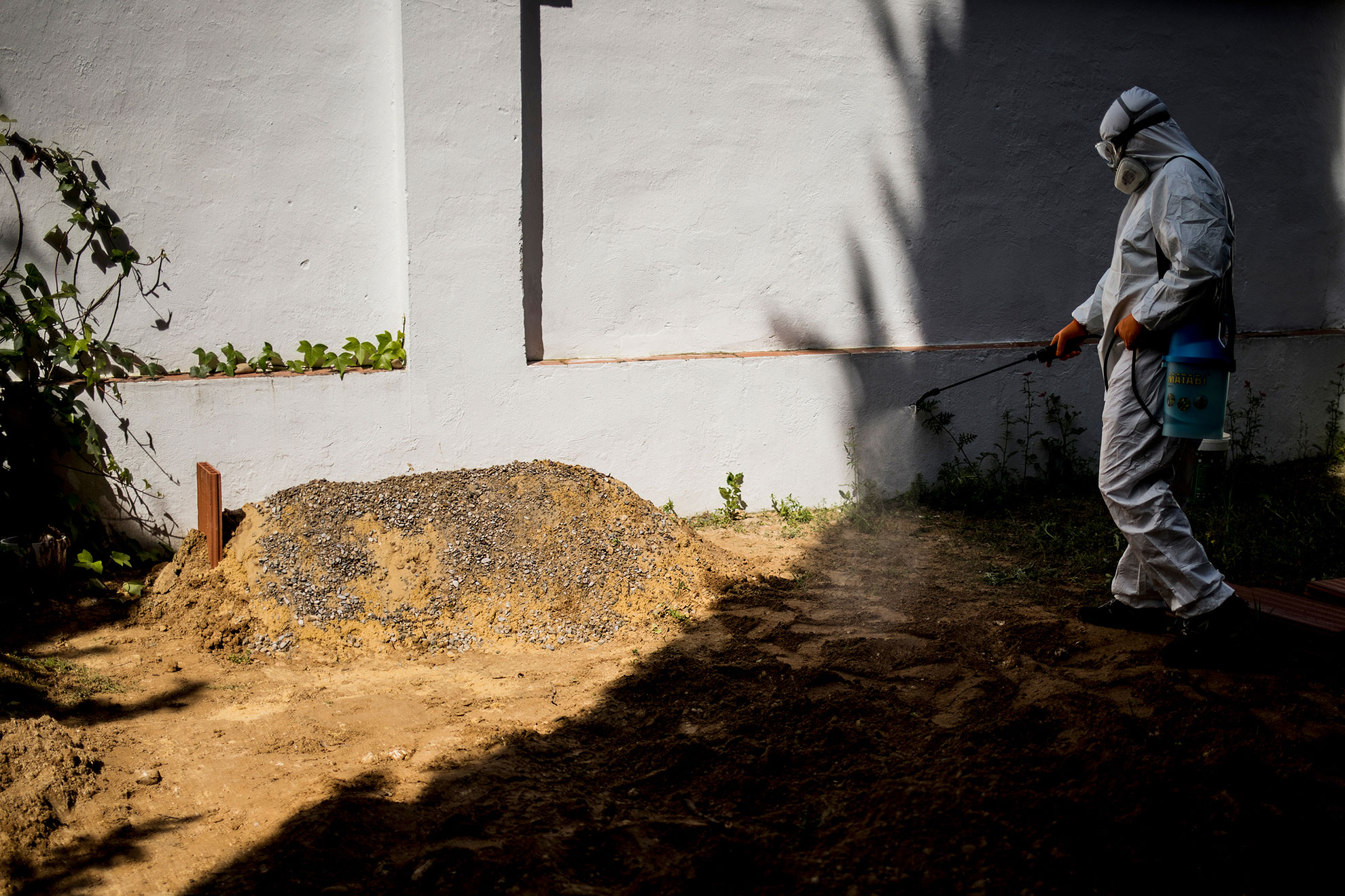 Un operario desinfecta la tumba recién enterrada de una persona fallecida a causa de complicaciones por la infección del virus COVID-19. Jerez, 4 de abril, 2020.