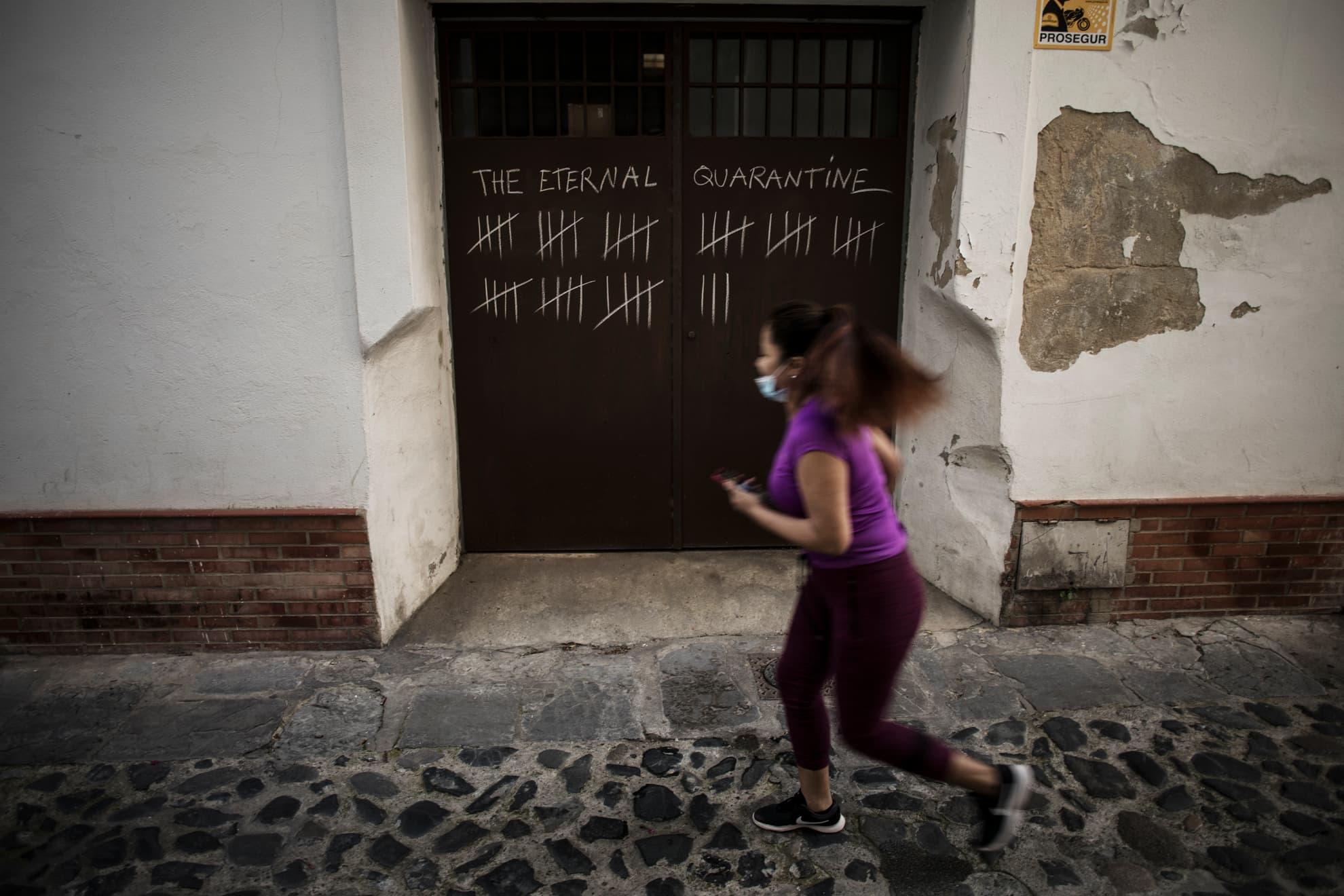 """La artista Julia Sangil, de 21 años, tuvo que dejar la universidad y regresar a casa de su familia en Jerez debido a la pandemia producida por la COVID-19. Tras días confinada, tenía la sensación de no saber en qué día vivía, todos los días eran iguales, lo que le inspiró para realizar una cuenta de cada uno que pasaba en la puerta del garaje de su casa con tiza, que ahora luce públicamente 53 días más tarde, y sumando. Eligió el estilo """"carcelario"""", ya que es así cómo siente la situación. En la imagen, una mujer corre delante de su obra en Jerez, el 5 de mayo, 2020."""