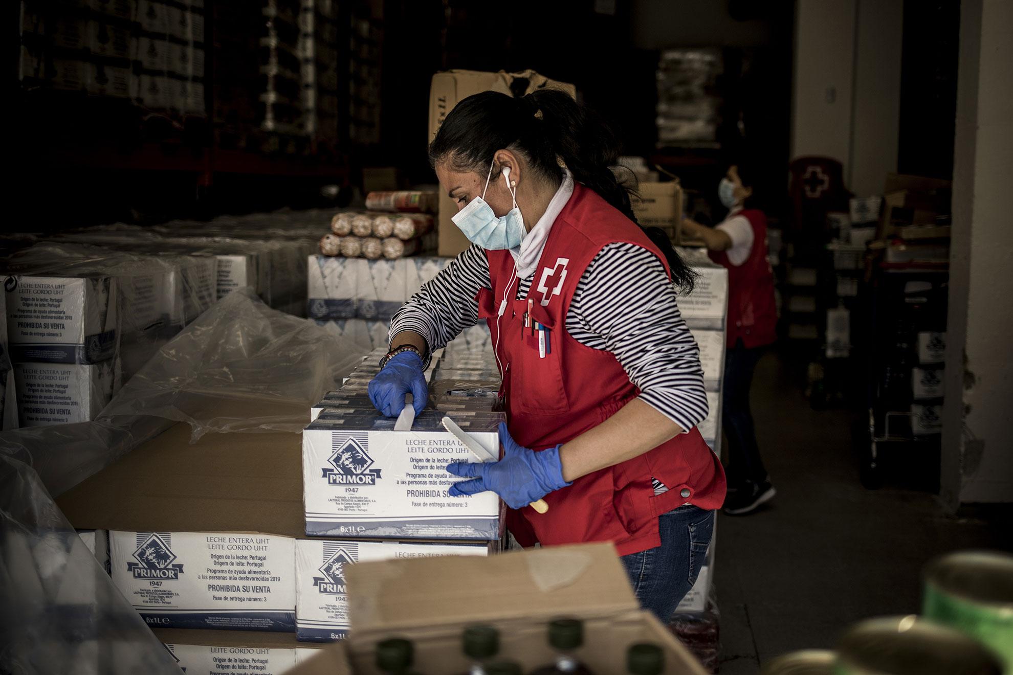 Voluntarios de Cruz Roja en Jerez ordenan el almacén de alimentos y productos de primera necesidad que están facilitando a personas en riesgo de exclusión social, como personas sin hogar y familias sin recursos, haciéndoles llegar kits de alimento e higiene a sus domicilios a aquellas personas que cuentan con problemas de movilidad.