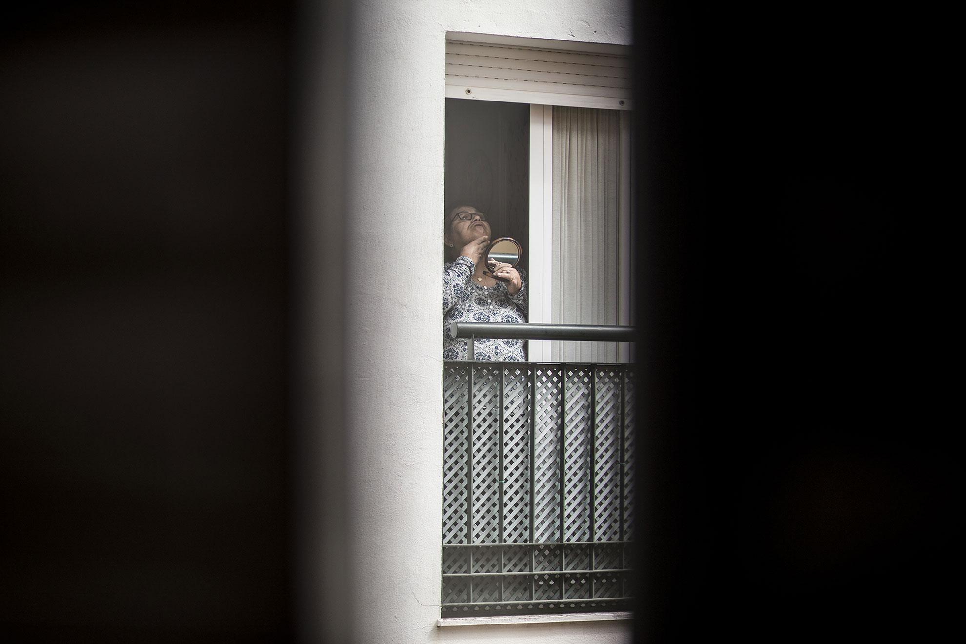 Una mujer usa un espejo en la ventana de su piso en Jerez de la Frontera, España, el 14 de Marzo, 2020. El gobierno español decretó el estado de alarma con confinamiento domiciliario el día anterior, 13 de marzo, para evitar la propagación del COVID19.