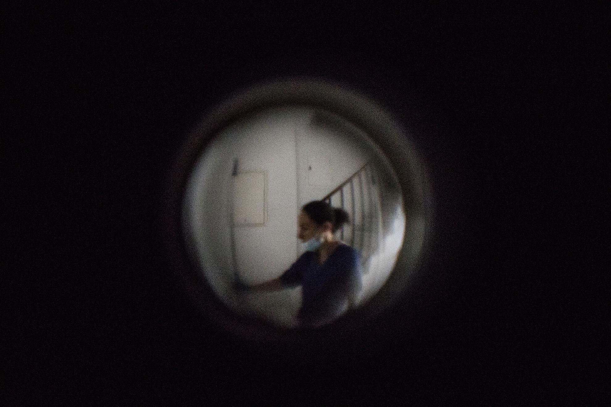 Una empleada del servicio de limpieza vista a través de la mirilla de una puerta lleva una máscara para protegerse de la infección por COVID19 en Jerez, España, el 17 de marzo 2020. El gobierno español declaró el estado de alarma y ordenó el confinamiento domiciliario debido al brote de COVID19 el pasado viernes día 13 de Marzo.
