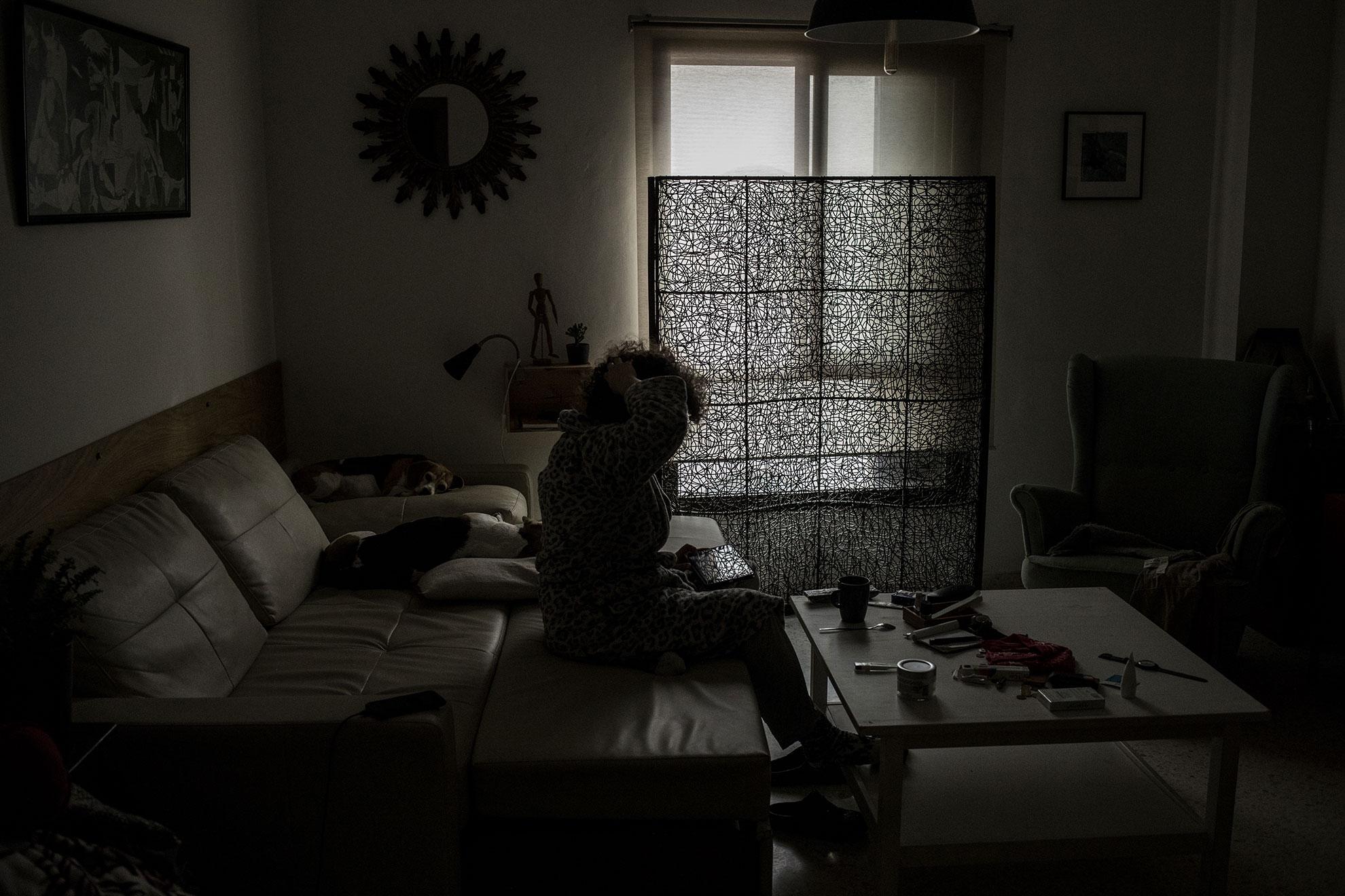T.A. consulta las noticias en una tableta mientras toma un café en la mañana del quinto día de confinamiento domiciliario en Jerez, España, el miércoles 18 de marzo de 2020.