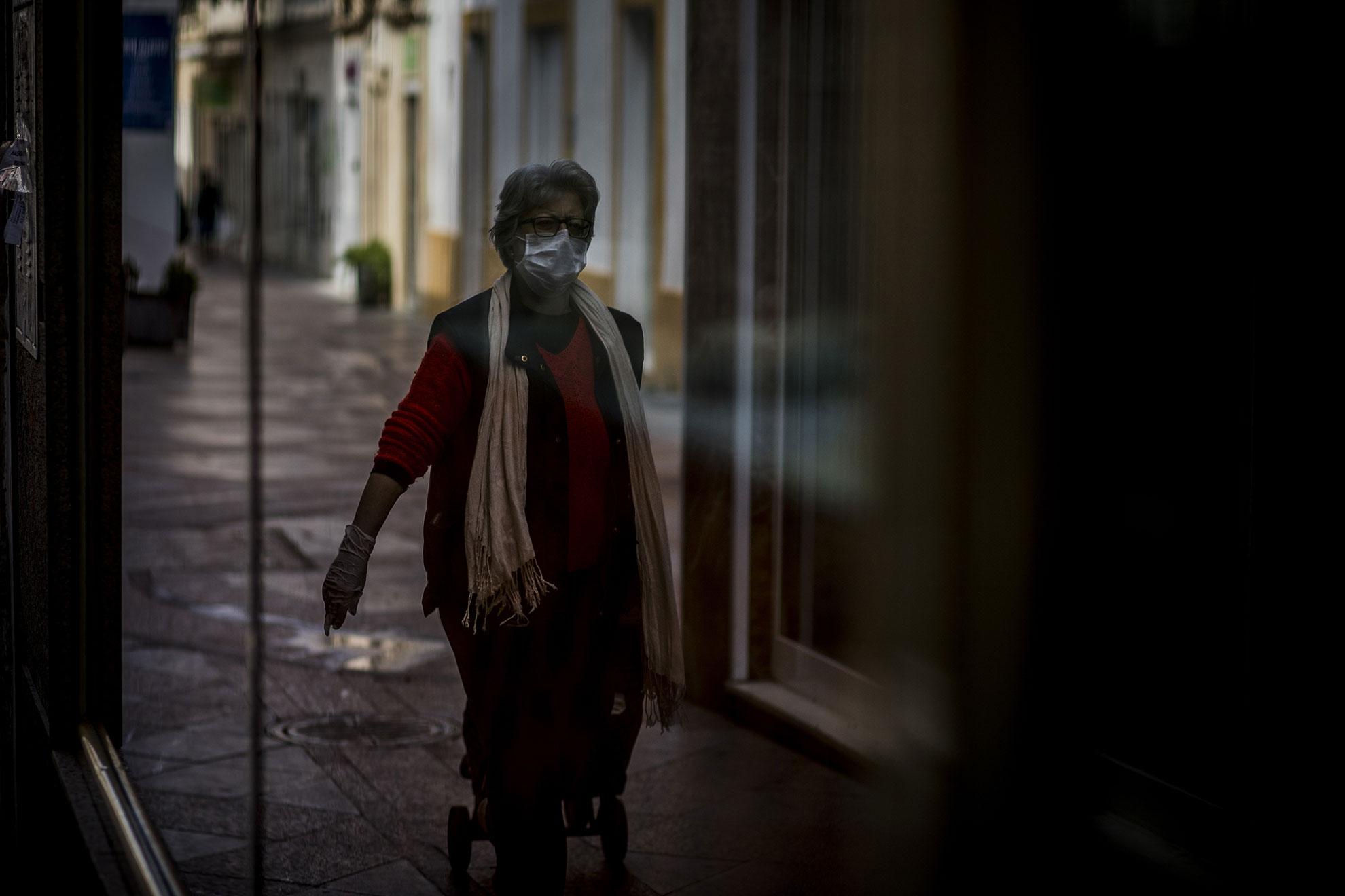 Sacar a pasear el perro o hacer la compra, labores que antes del confinamiento podían llegar a ser poco satisfactorias, se han convertido en momentos ansiados en los hogares andaluces. En la imagen, una mujer se dirige a realizar la compra con mascarilla y guantes en Jerez.