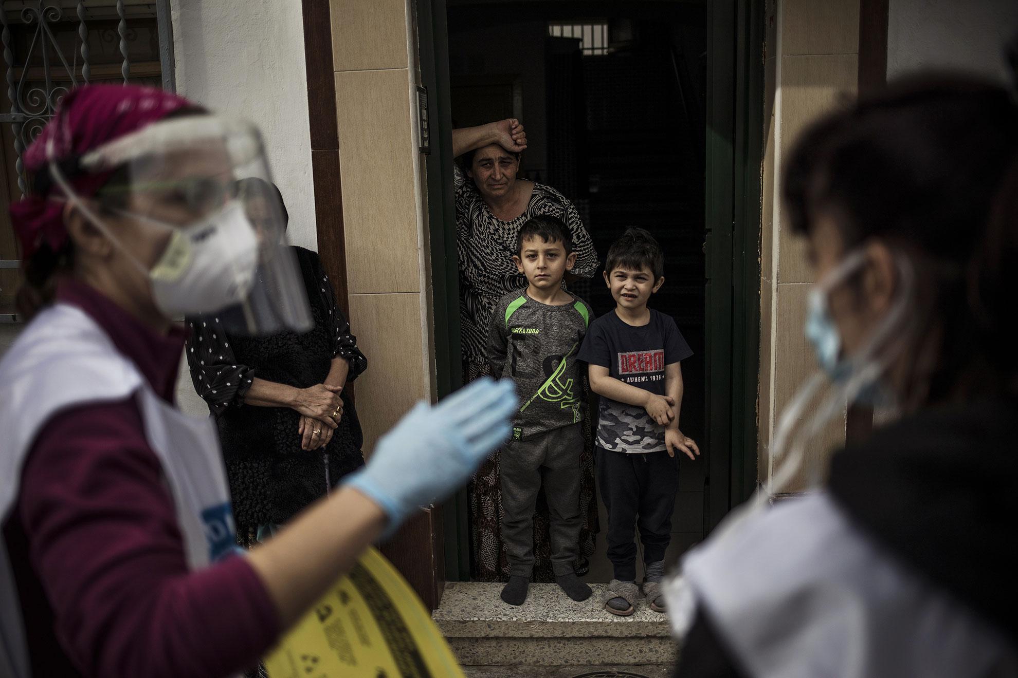 Miembros de una familia gitana-rumana escuchan instrucciones sobre cómo evitar la infección por coronavirus que detalla un médico voluntario de la ONG española Médicos del Mundo, en la puerta de su hogar en Granada, España, como parte de una campaña de información y sensibilización sobre el COVID-19 al colectivo.