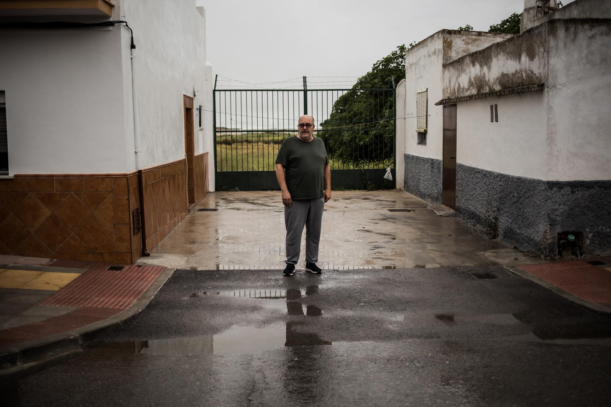José Díaz, de 56 años, es natural de El Cuervo, Sevilla, pero aparca su coche en la provincia de Cádiz, frente a su casa. Vive en la Avenida de Cádiz del pueblo sevillano, antigua cañada real, que a partir del número 68 pasa a pertenecer a la provincia de Cádiz. Ambas provincias pasan mañana a Fase 1 de la desescalada programada por el gobierno de España por la pandemia de COVID-19, que impide viajar entre provincias, aunque resultará difícil seguir esta norma para los vecinos que habitan aquí ya que cada día cruzan la calle, o sea, de una provincia a otra para comprar el pan, ir al banco o la farmacia. Esta situación administrativa no es nueva, llevan décadas así, vecinos que tributan en diferentes municipios o votan en elecciones en lugares diferentes. En la imagen, José con un pie en Cádiz y otro en Sevilla, frente a su hogar.