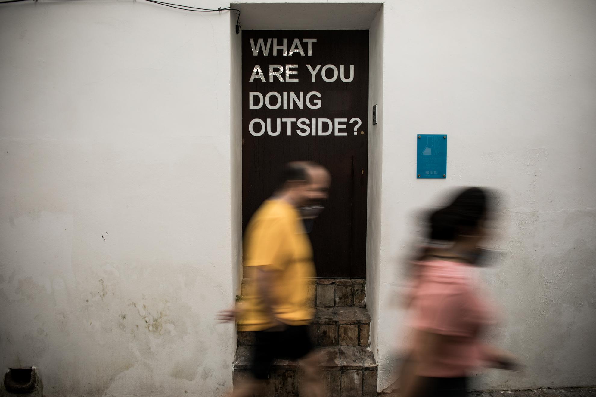 """Ayer fue el primer día de la Fase 1 de desescalada del confinamiento en España a causa de la pandemia por COVID-19 y sorprenden escenas como aglomeraciones en terrazas de bar, besos, abrazos... En la imagen: la leyenda """"¿Qué haces fuera?"""" luce en la puerta de una guardería en Jerez."""