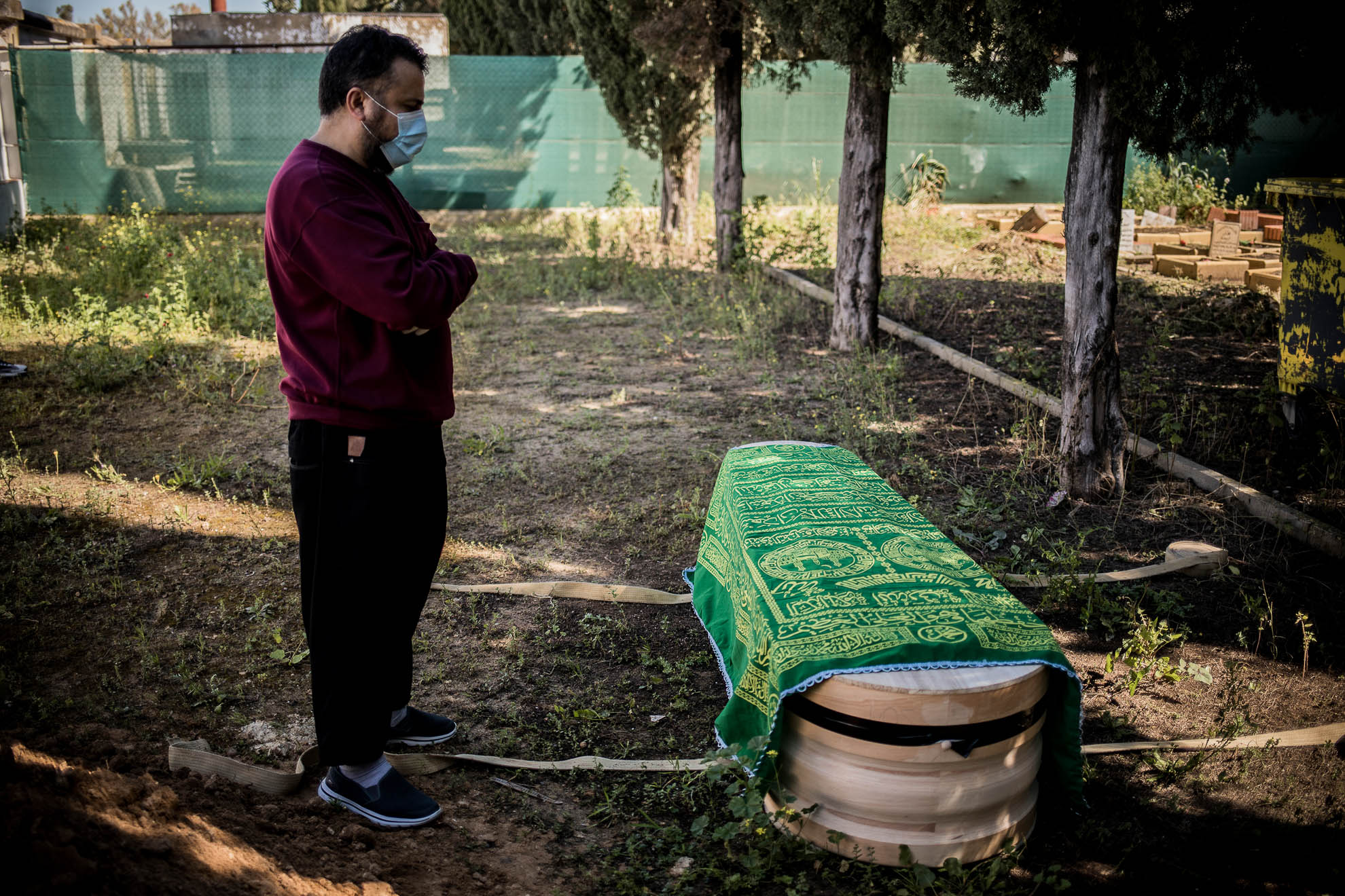 Ibrahim Elilo, imán en la mezquita de Jerez, reza frente al ataúd de un varón marroquí de 77 años fallecido a causa del COVID-19 en el cementerio, momentos antes de ser enterrado.