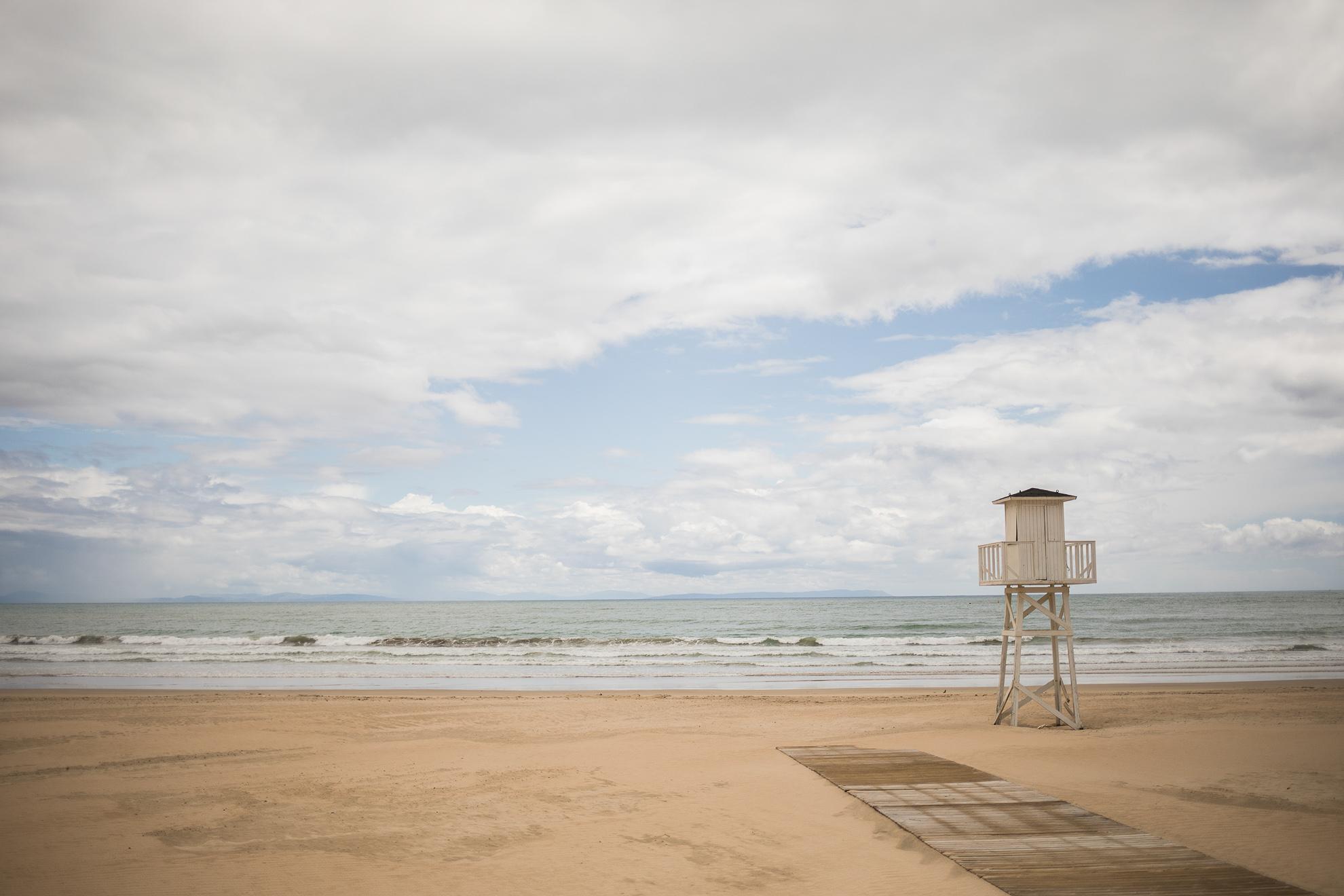 Mañana se pasa a Fase 2 de la desescalada en el confinamiento por la pandemia en muchos lugares, como el caso de la provincia de Cádiz. Entre otras actividades, se podrá disfrutar del baño en muchas de las playas de la provincia que, hasta ahora, permanecían vacías. Siendo los 138 kilómetros de playa de arena fina el principal atractivo turístico de la provincia y experimentando ya temperaturas superiores a los 30º C, se espera una gran afluencia de personas. Algunos ayuntamientos trabajan en la implantación en medidas de control de aforo, otros en ampliar el periodo de prohibición del baño hasta más adelante. En la imagen, la playa de Barbate completamente vacía de personas.
