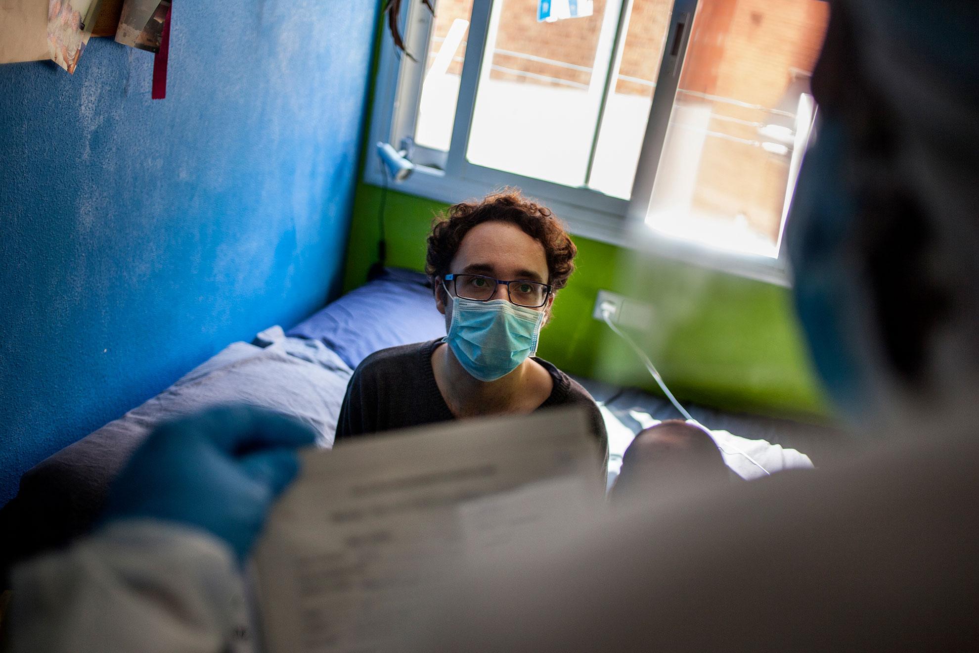 Un chico que presentaba síntomas leves , en la habitación de su casa, es atendido por un sanitario que le explica y realiza las pruebas para el ensayo clínico en el que colaboran los trabajadores humanitarios de la ONG española Open Arms y que llevan a cabo pruebas de detección de coronavirus en el hogar de ancianos y en hogares privados en Cataluña, España. La iniciativa es parte de un ensayo clínico dirigido por los médicos Oriol Mitja y Bonaventura Clotet, de la Fundación Lluita contra el SIDA y el Hospital Germans Trias, centrados en reducir la transmisión del virus. España ha visto el jueves un nuevo récord en muertes relacionadas con virus que se produjo cuando el país está viendo disminuir el contagio, los datos del Ministerio de Salud mostraron que España se encuentra cara a cara con Italia, el país que vio el peor brote en Europa. El coronavirus COVID-19 causa síntomas leves o moderados para la mayoría de las personas, pero para algunos, especialmente los adultos mayores y las personas con problemas de salud existentes, puede causar enfermedades más graves o la muerte.