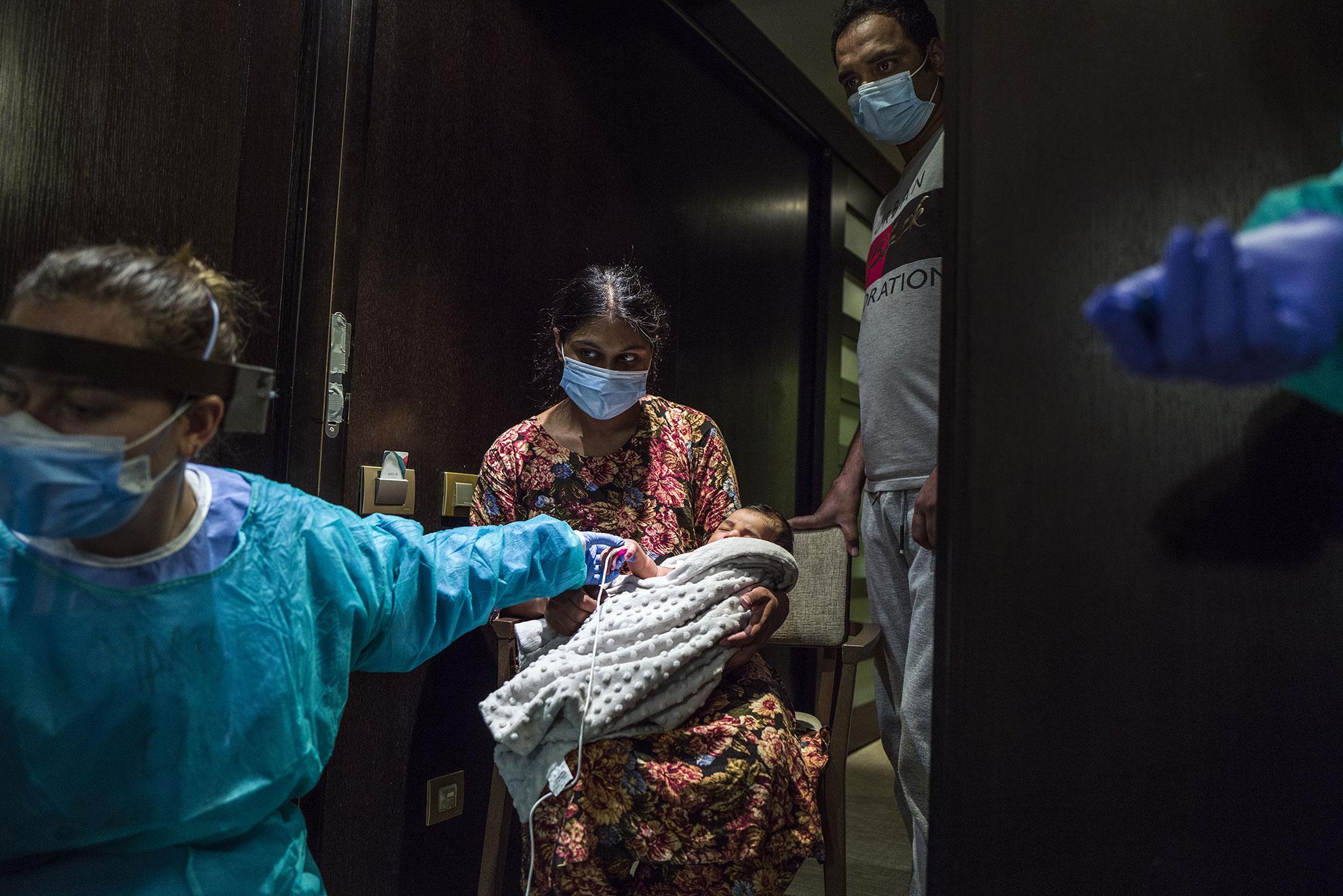 """""""La vida sigue"""". Enfermeras de la atención primaria de Barcelona, del Instituto Catalán de la Salud, monitoreando a un bebe de semanas de vida, después de tomarle la temperatura a sus padres, recuperándose de estar enfermos de Covid-19. Están en cuarentena en el Hotel Melià de Barcelona. Pacientes enfermos de Covid-19 dados de alta hospitalaria han sido trasladados a diferentes hoteles de Barcelona, entre ellos el Hotel Melià, para pasar dos semanas de confinamiento, antes de poder volver a casa. Una vez llegan, personal sanitario y del hotel hacen la acogida y toma de temperatura antes de asignarles una habitación."""