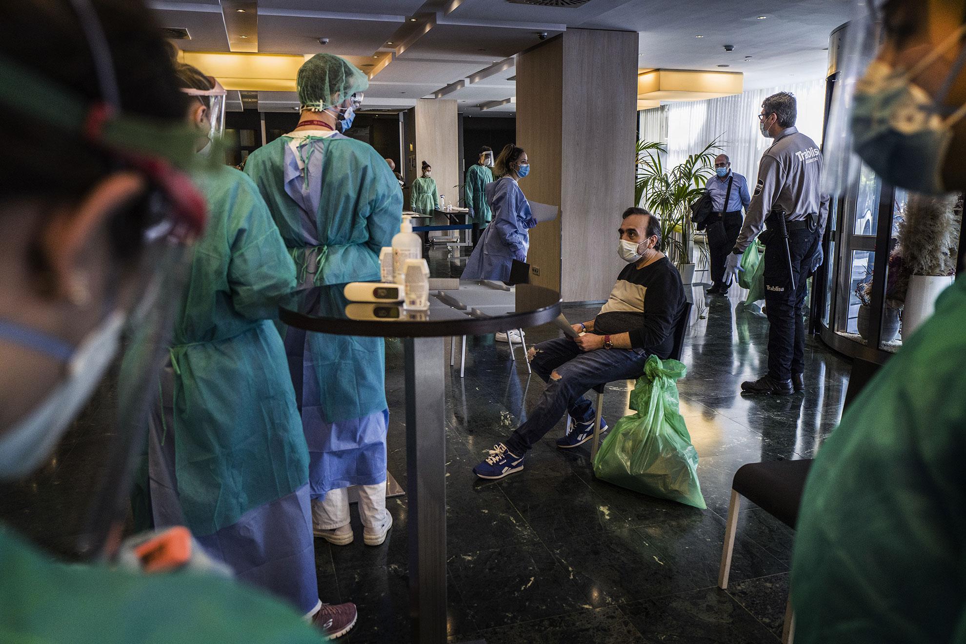 Enfermeras y enfermeros de la atención primaria de Barcelona, del @icscatalunya (Instituto Catalán de la Salud), recibiendo en la recepcion del Hotel Melià , e iniciando el protocolo de entrada a los pacientes que acaban de llegar del hospital, por de estar enfermos de Covid-19 . Y que son hospedado en el Hotel. Pacientes enfermos de Covid-19 dados de alta hospitalaria han sido trasladados a diferentes hoteles de Barcelona, entre ellos el Hotel Melià, para pasar dos semanas de confinamiento, antes de poder volver a casa. Una vez llegan, personal sanitario y del hotel hacen la acogida y toma de temperatura antes de asignarles una habitación.