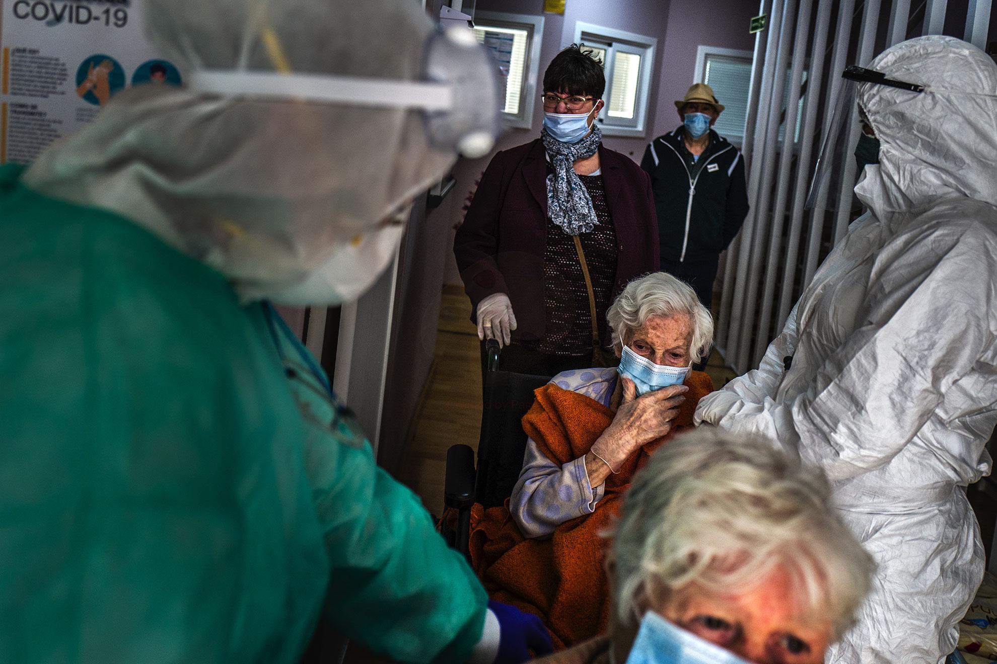 Unos trabajadores de la ONG española Open Arms esperan en la recepción de una residencia con un grupo de ancianos , no positivos a COVID-19, Barcelona, España. En los hogares de ancianos, se hace todo lo posible para mantener alejados a los visitantes que puedan estar infectados, y los miembros de la familia casi siempre tienen prohibido ir a ver a sus seres queridos.