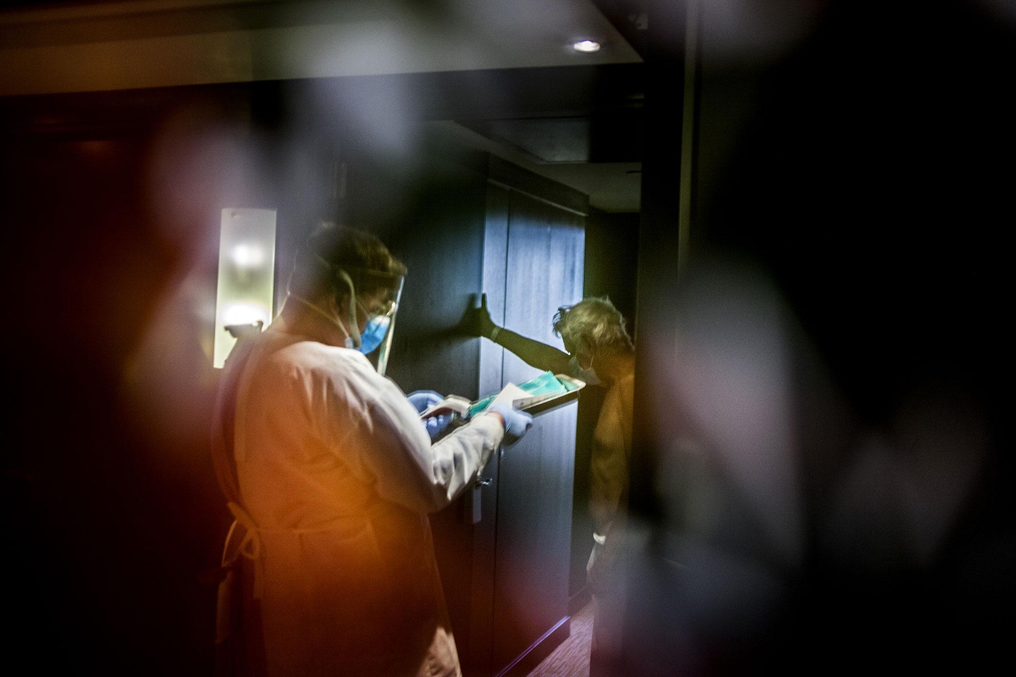 Un enfermero de la atención primaria de Barcelona, del @icscatalunya (Instituto Catalán de la Salud), habla con un señor después de tomarle la temperatura en el Hotel Melià de Barcelona. Pacientes enfermos de Covid-19 dados de alta hospitalaria han sido trasladados a diferentes hoteles de Barcelona, entre ellos el Hotel Melià, para pasar dos semanas de confinamiento, antes de poder volver a casa. Una vez llegan, personal sanitario y del hotel hacen la acogida y toma de temperatura antes de asignarles una habitación.