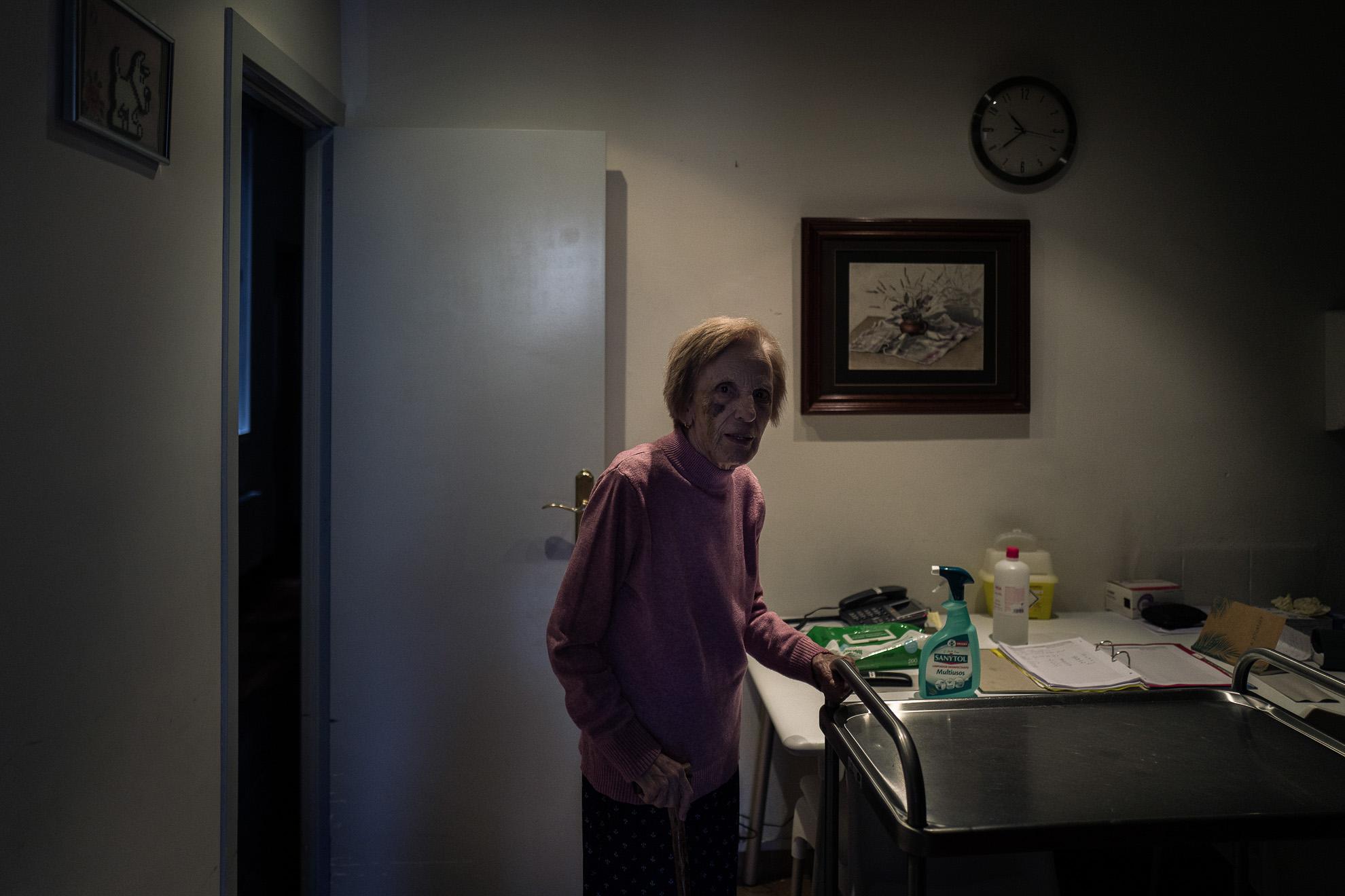 """La señora Irene Azpiroz se acerca a la cocina de uno de los pisos en la residencia Centro Geriàtric Gure-Etxea.// """"Envejecer es como escalar una gran montaña; mientras se sube, las fuerzas disminuyen, pero la mirada es más libre, la vista más amplia y serena."""" –Ingmar Bergman"""