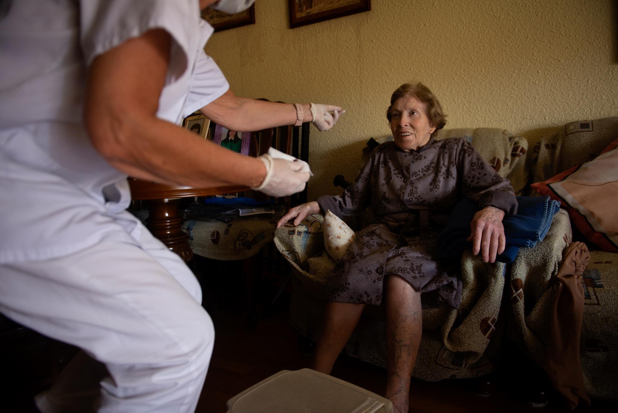 Teresa es enfermera y atiende a Paula en su domicilio. Todos los días visita a los pacientes de más edad para que no tengan que asistir al centro de salud y puedan permanecer confinados y seguros en sus casas.