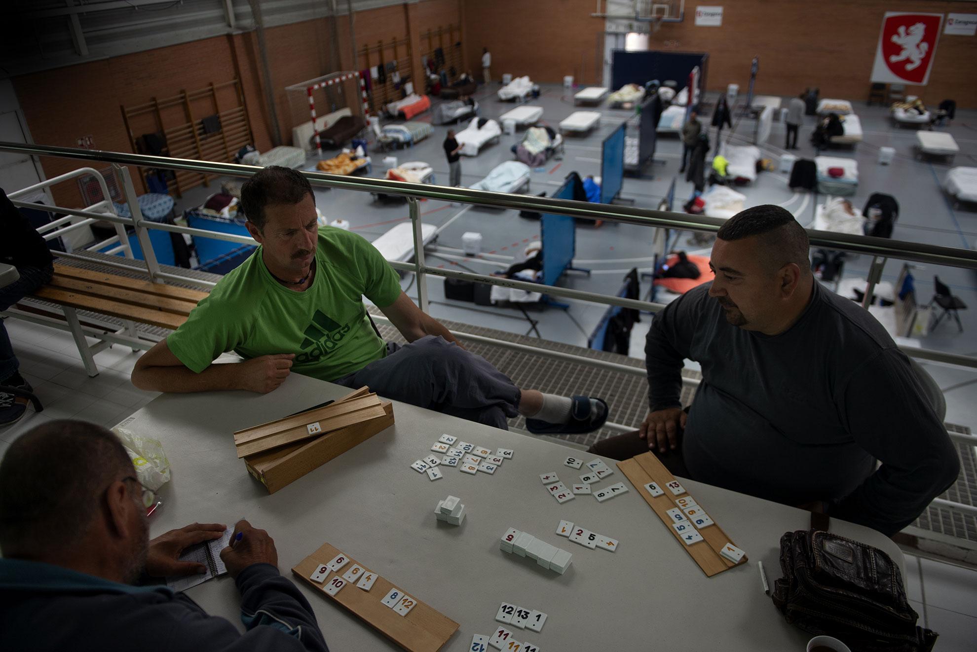 Florin, Christian y Jon juegan al Rummykub mientras permanecen confinados en el Pabellón deportivo Tenerías habilitado por el Ayuntamiento de Zaragoza para acoger a las personas sin alojamiento en la ciudad durante el estado de alarma.