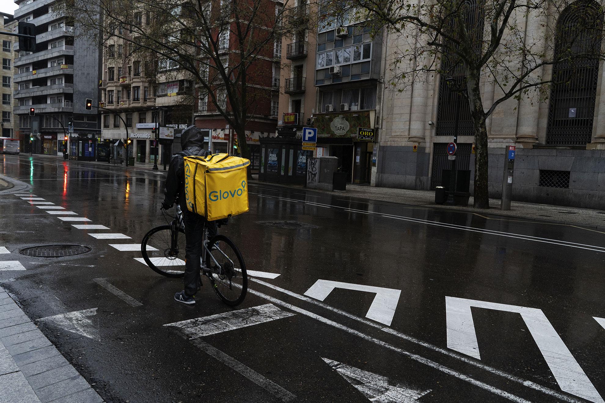 Repartidor de Glovo trabajando en las calles vacías del centro de Zaragoza.