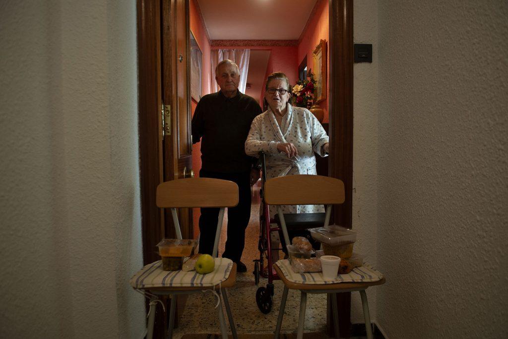 Pilar y su marido permanecen confinados en casa desde que se decretó el estado de alarma. Debido a su edad y sus circunstancias no pueden salir a la compra ni tampoco realizar muchas de las tareas del hogar como cocinar. Se han acogido al programa de reparto de comida a domicilio que gestiona Cruz Roja en Huesca. Tres días a la semana reciben la comida y la cena ya cocinada para dos días. La entrega se realiza con la mayor seguridad posible para ellos colocando dos sillas en la puerta donde se depositan las bandejas con los alimentos para evitar el contacto directo.