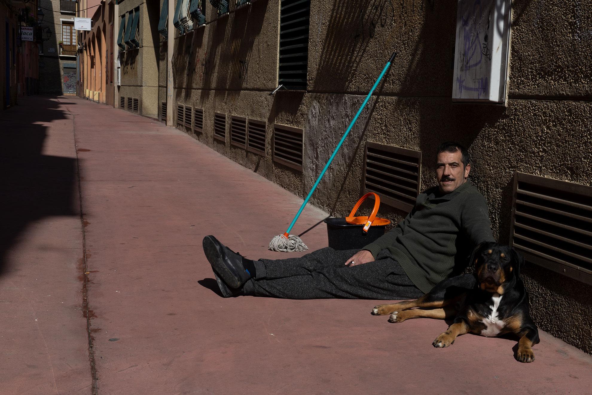 José Luis y su perro frente a la puerta de su casa después de haber limpiado las zonas comunes del edificio donde viven. Esperan a que se seque la escalera para volver a casa. Las comunidades de vecinos extreman las precauciones en la higiene de los edificios para protegerse de contagios.