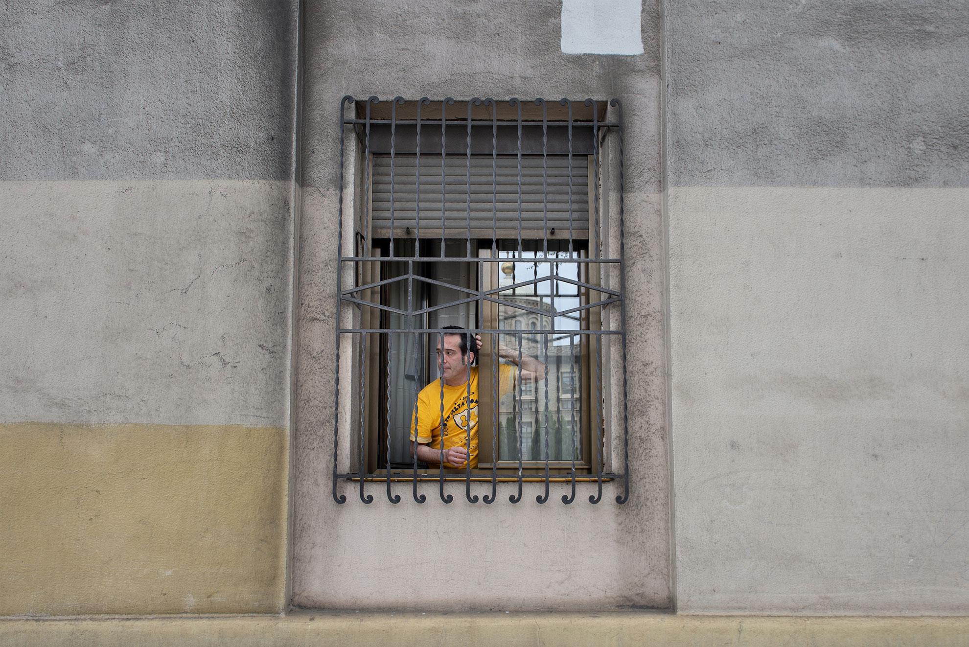 Felipe asomado a su ventana con rejas en una céntrica calle de Zaragoza, en el décimo día confinamiento de la población en sus casas.