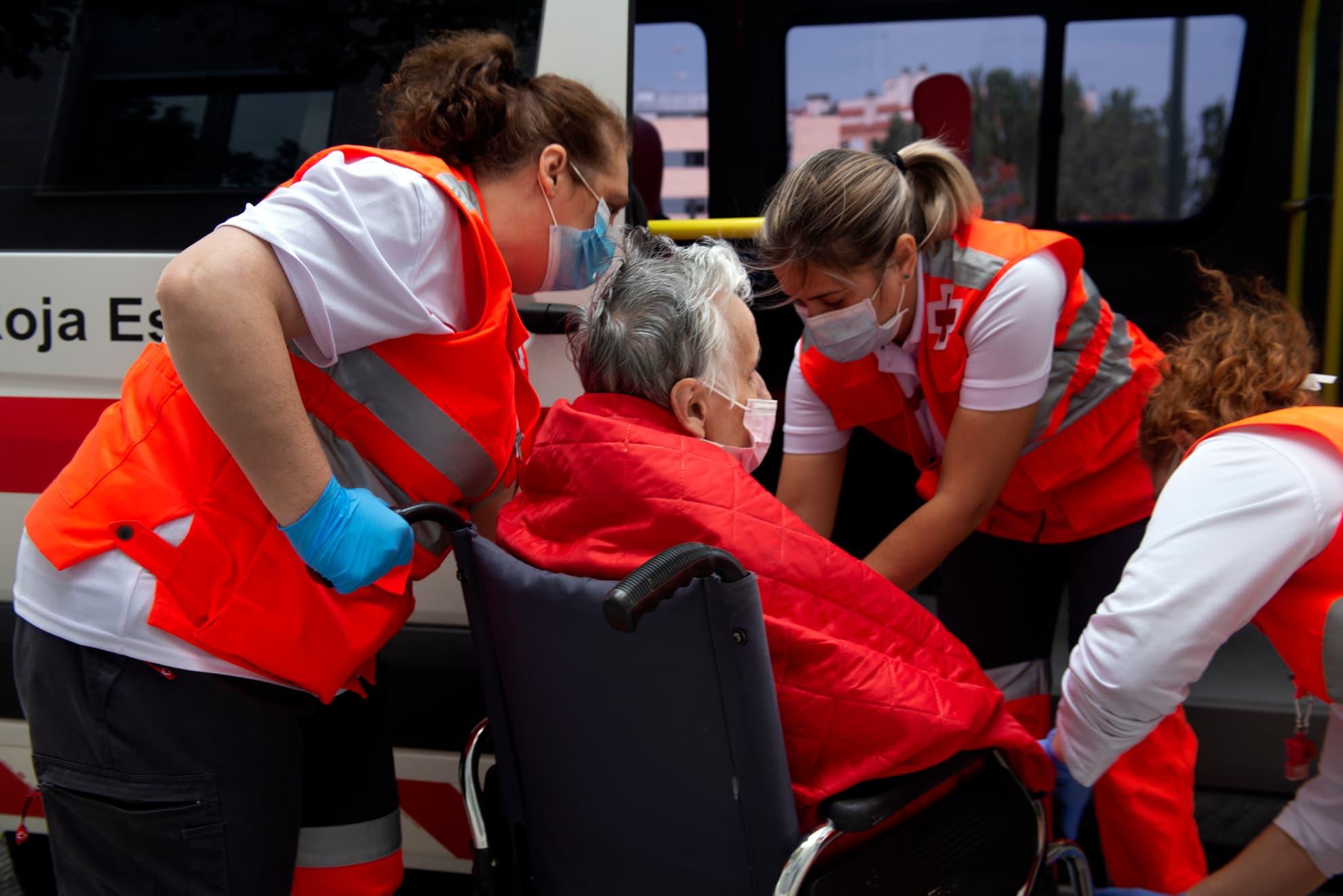 Voluntarias de Cruz Roja trasladan a una mujer que, tras pasar varias semanas en una residencia habilitada por el Gobierno de Aragón para atender a personas mayores con coronavirus, al fin puede regresar a su residencia habitual tras dar negativo en la prueba.
