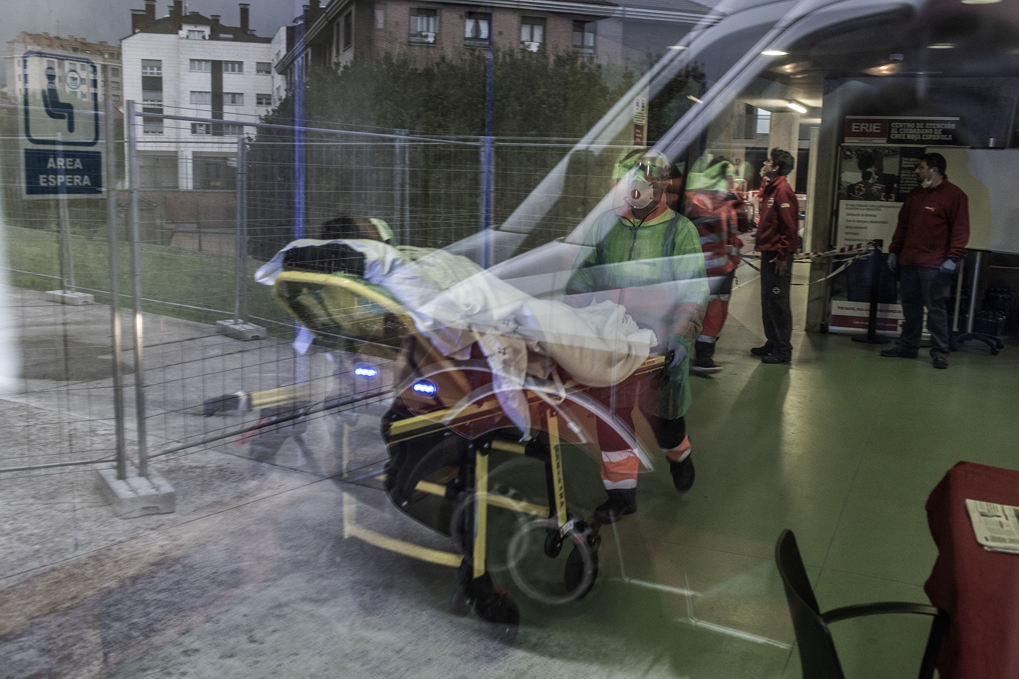 Una mujer sin hogar es llevada a la ambulancia después de presentar una crisis respiratoria con saturación muy baja de oxigeno en un refugio temporal creado por las autoridades locales y la Cruz Roja en Gijón, Asturias.