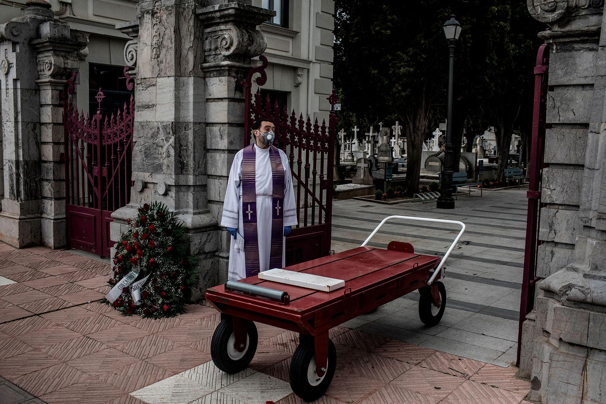 En esta foto tomada el pasado 8 de Abril del 2020: El párroco Manuel Flaker espera a la puerta del cementerio cerca del carro para transportar ataúdes antes de la inhumación de D. Marcial Souto, 82, en el cementerio de León, España. 13 Abril, 2020 @manubrabo Parroco y asociado han venido al funeral en calidad de amigos de la familia y para dar un responso y apoyo a Jose Manuel, hijo y único asistente al entierro, pues su madre está delicada de salud y su hermana vive en el extranjero, en Irlanda.