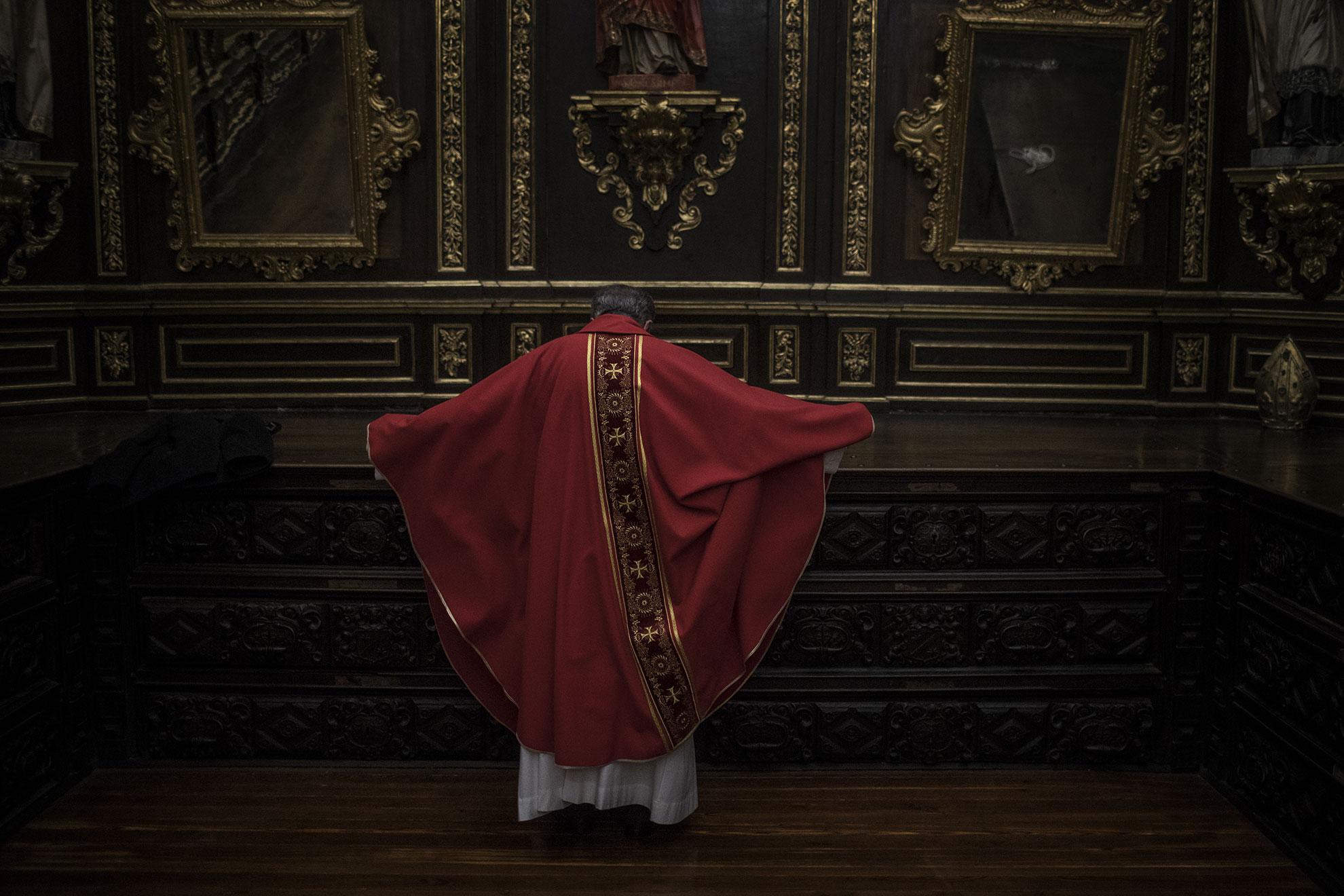 En esta foto tomada el pasado 10 de abril un cura se viste antes de la Misa del Martirio de Viernes Santo en sacristía de la catedral de Zamora, España.