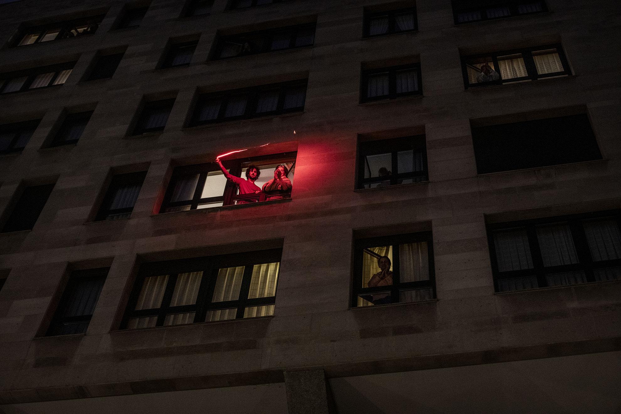 Como cada día desde el principio de esta crisis, habitantes de Gijón (como cualquier otro ciudadano español) se asoma a la ventana para aplaudir y animar a los trabajadores del sistema publico de salud, primera linea contra el COVID19. En la foto, un joven agita un cordon de luz roja mientras la gente aplaude al personal del centro de salud situado en la Plaza Zarracina, en el Centro de Gijón, España.