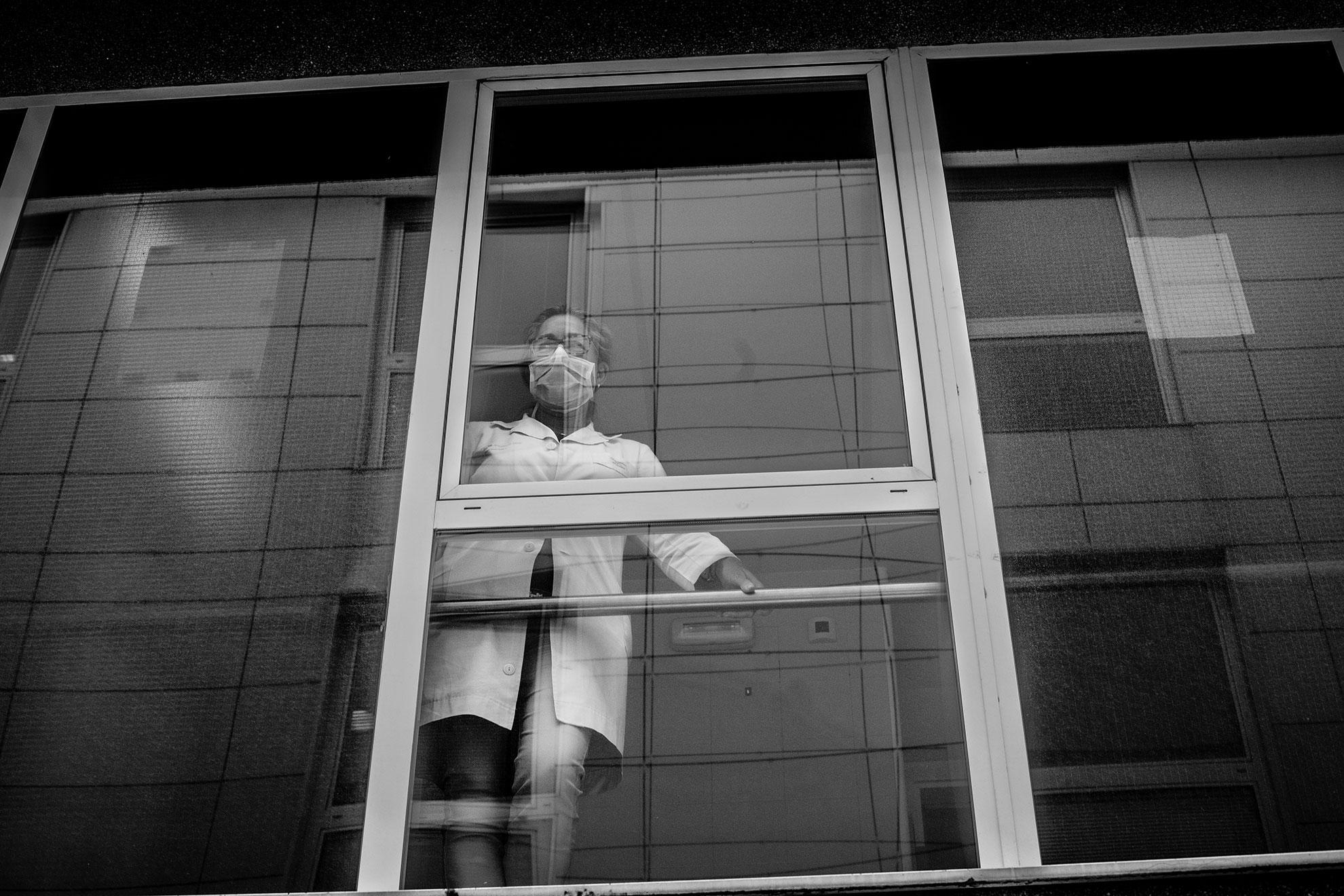 En esta foto realizada el 19 de marzo de 2020, una trabajadora del hospital Universitario de Gijón observa los trabajos de desinfección realizados por miembros de la UME (Unidad Militar de Emergencias) en el exterior del complejo. Gijón, Asturias, España.
