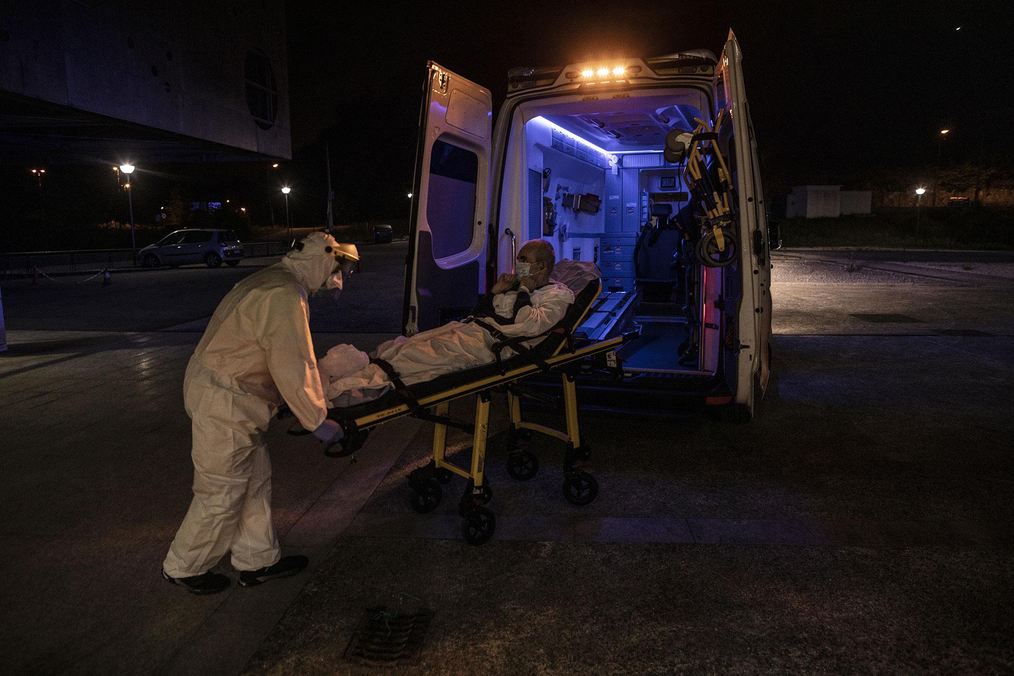 Santos, un paramédico, transporta a José María, un paciente con COVID-19, desde la ambulancia al centro de enfermedades neurológicas, autorizado en la cuenca minera para recibir pacientes con síntomas leves de toda Asturias. Langreo, Asturias, España.