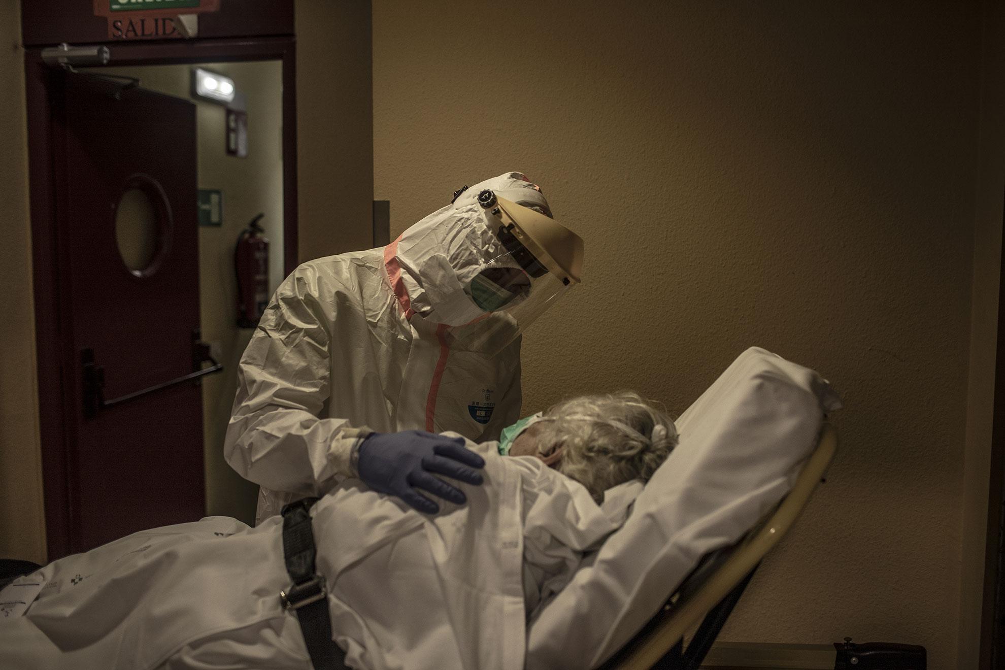 Pablo, un paramédico del servicio de ambulancia, habla con una mujer con síntomas de COVID mientras la traslada del hogar de ancianos donde vive al Hospital de la Universidad Central de Asturias. A pesar de ser dado de alta hace casi un mes después de sufrir COVID-19, este paciente repite los síntomas. Oviedo, Asturias, España.