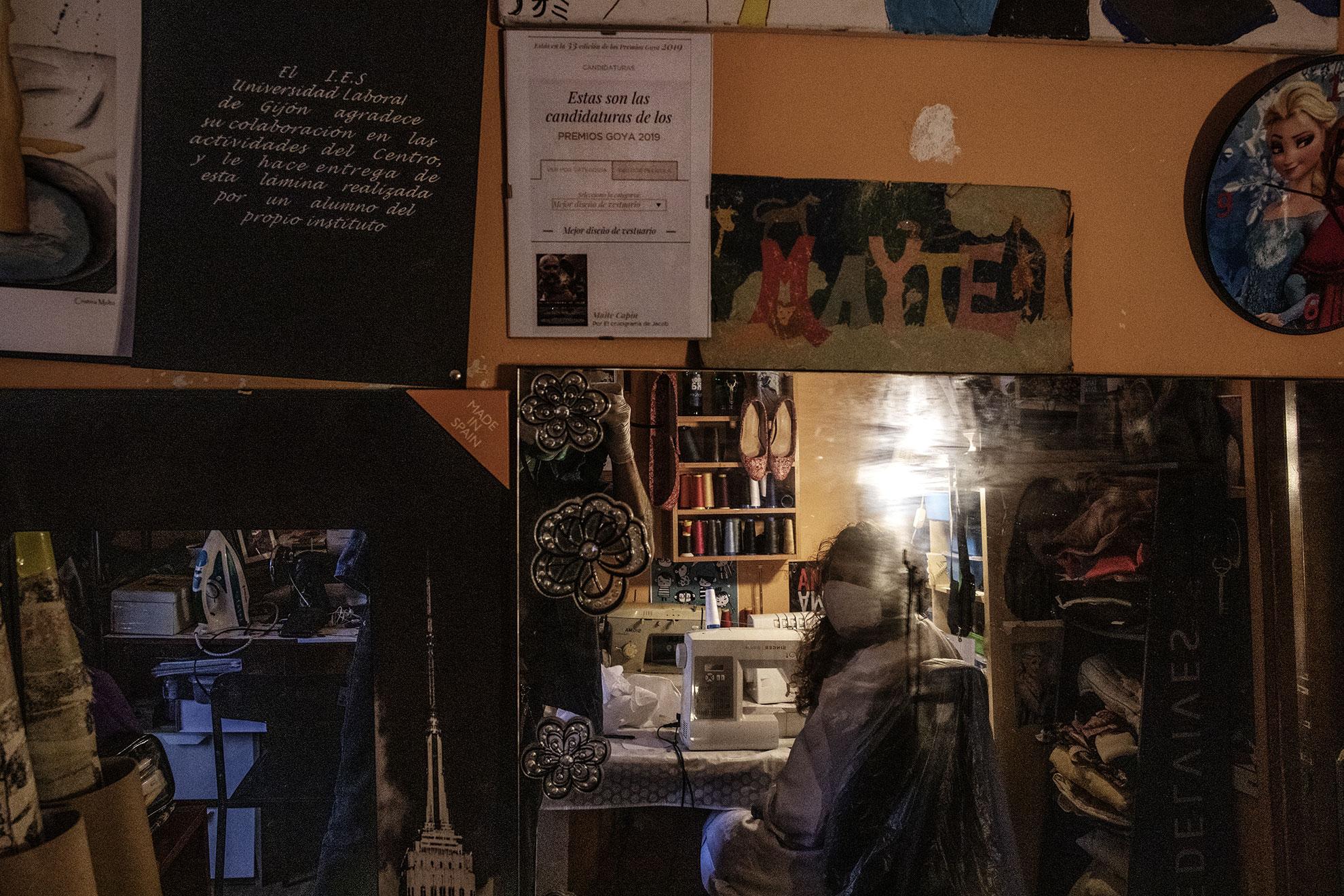 Maite Capín es directora de vestuario y ha estado nominada a los Goya el pasado año. Tan pronto se enteró de la falta de mascarillas organizo una red de costureras voluntarias para desarrollar mascarillas. Su método esta siendo seguido muy de cerca por las autoridades médicas de la ciudad, así como la facultad de enfermería de Oviedo, a fin de poder homologarlas y puedan ser distribuidas entre personal medico, apacientes y civiles por igual.En la foto: El diploma de las nominación a los premios Goya de 2019 cuelga de la pared del taller de costura mientras Maite se ve reflejada en un espejo. Oviedo, Asturias.