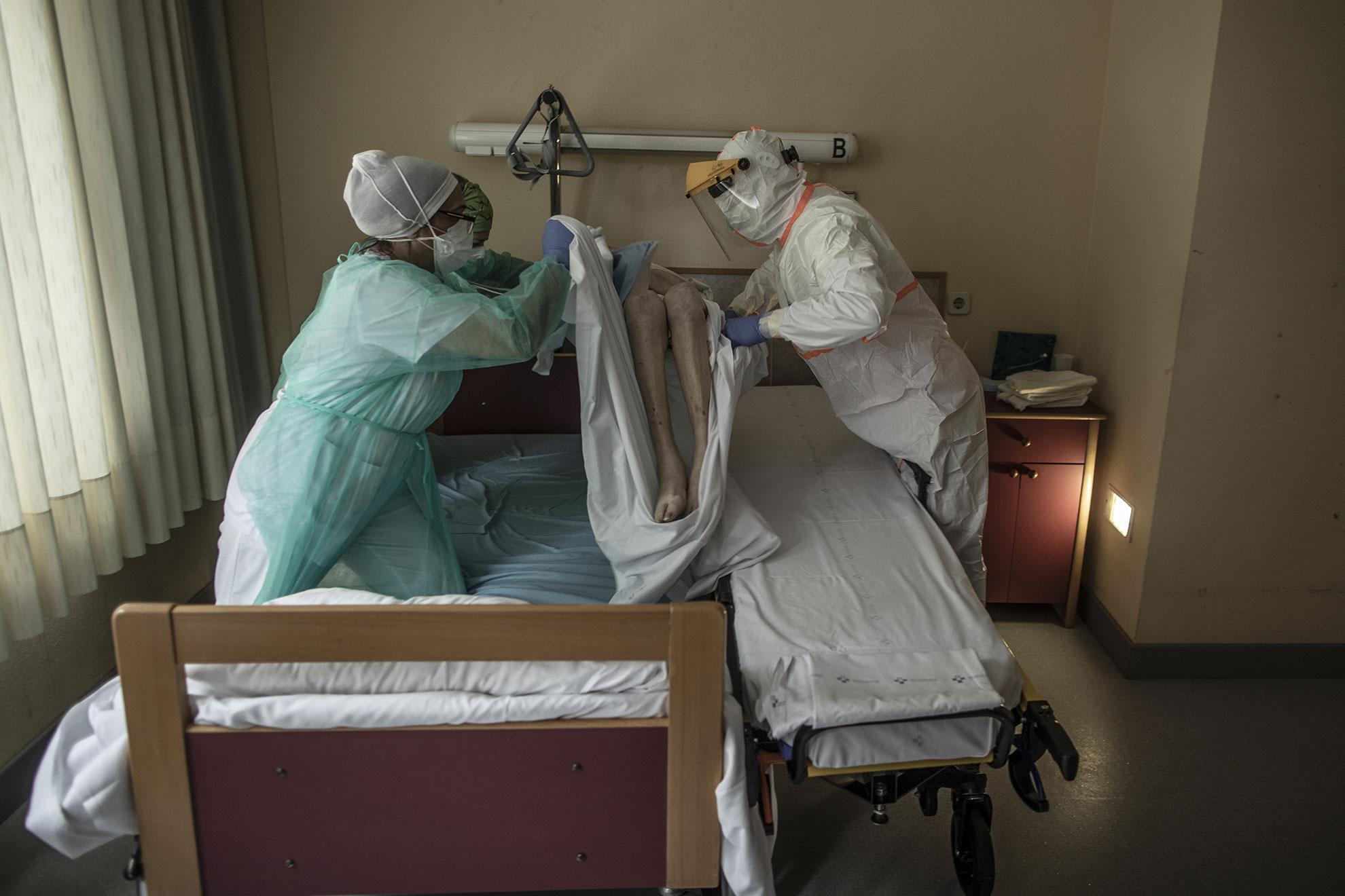 En esta foto tomada el pasado 23 de Abril, Pablo, un paramédico del servicio de ambulancia, y personal sanitario de una residencia de ancianos transfieren a una mujer con síntomas de COVID a una camilla para ser trasladada al Hospital de la Universidad Central de Asturias. A pesar de ser dada de alta hace casi un mes después de sufrir COVID-19, este paciente repite los síntomas. Oviedo, Asturias, España.