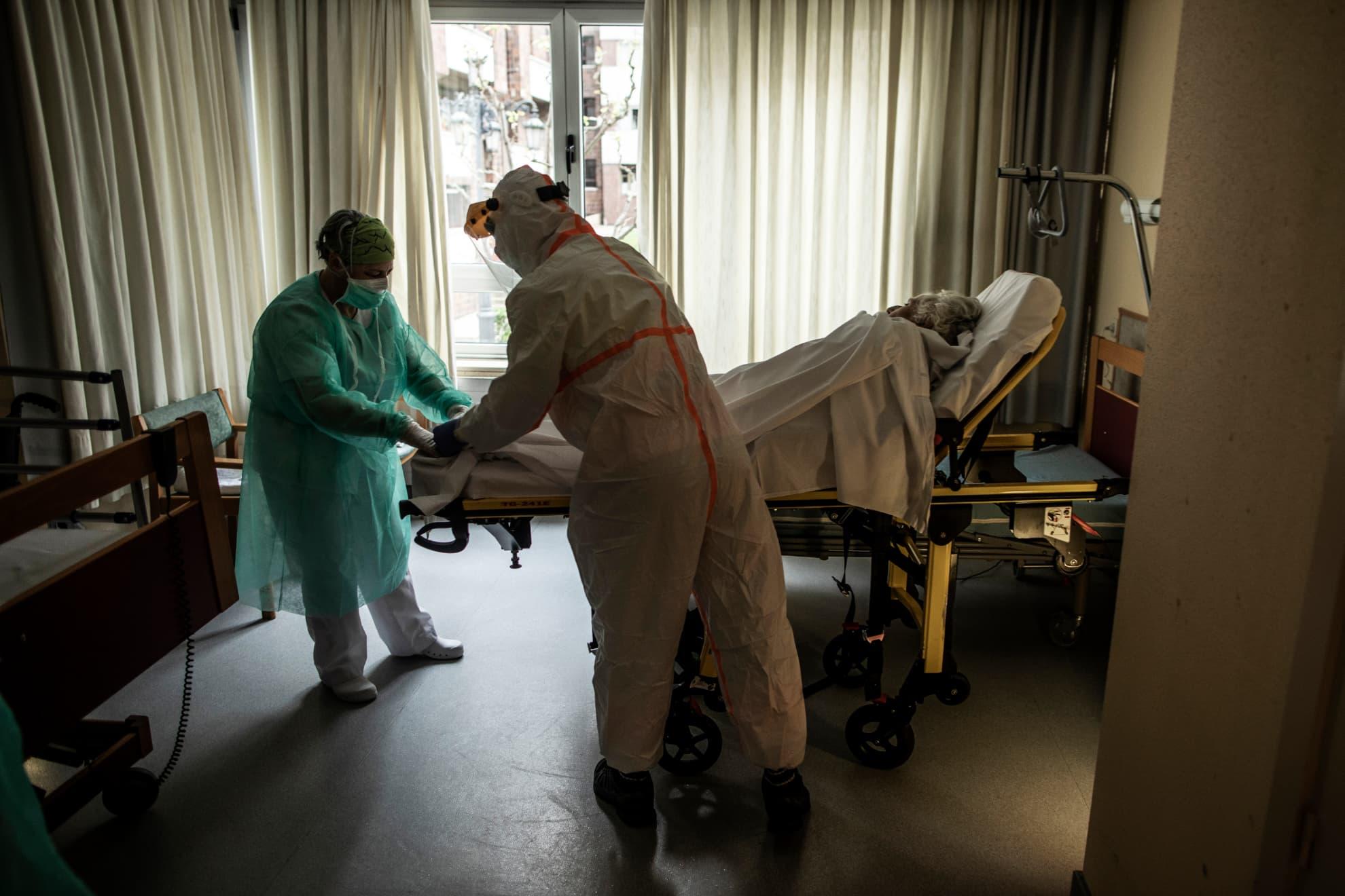 Durante el traslado al Hospital de la Universidad Central de Asturias, Pablo, un paramédico de ambulancia y una enfermera de la residencia de personas mayores sujetan a un anciano afectado con COVID-19. Oviedo, Asturias, España.