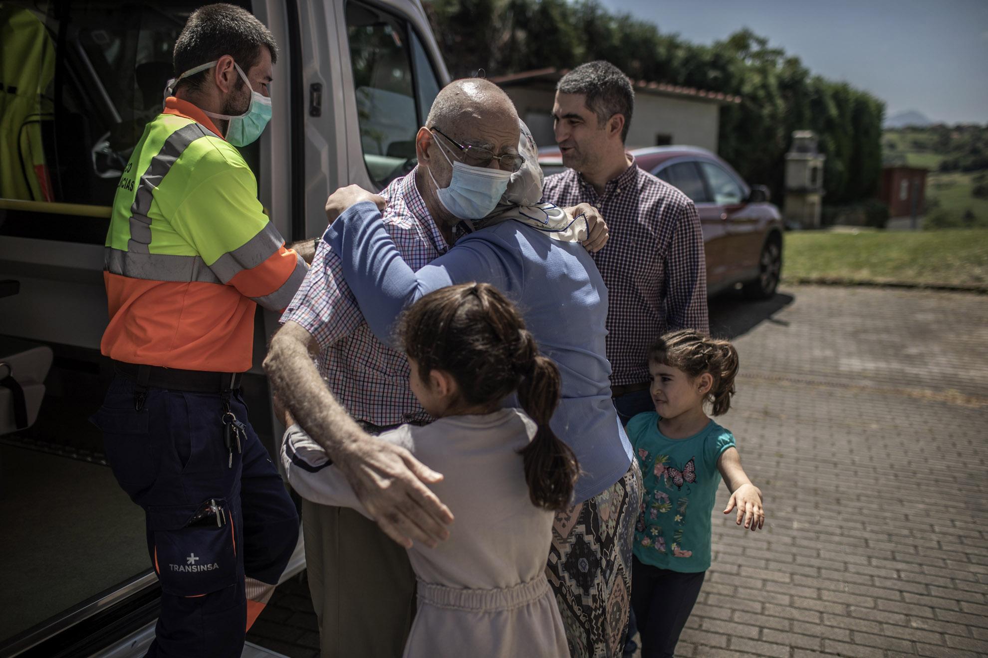 Después de dos meses en la UCI, el Dr. Yahia Zanabili, de 69 años, abraza a su esposa y a sus nietas al llegar a su casa en Oviedo, Asturias, España.