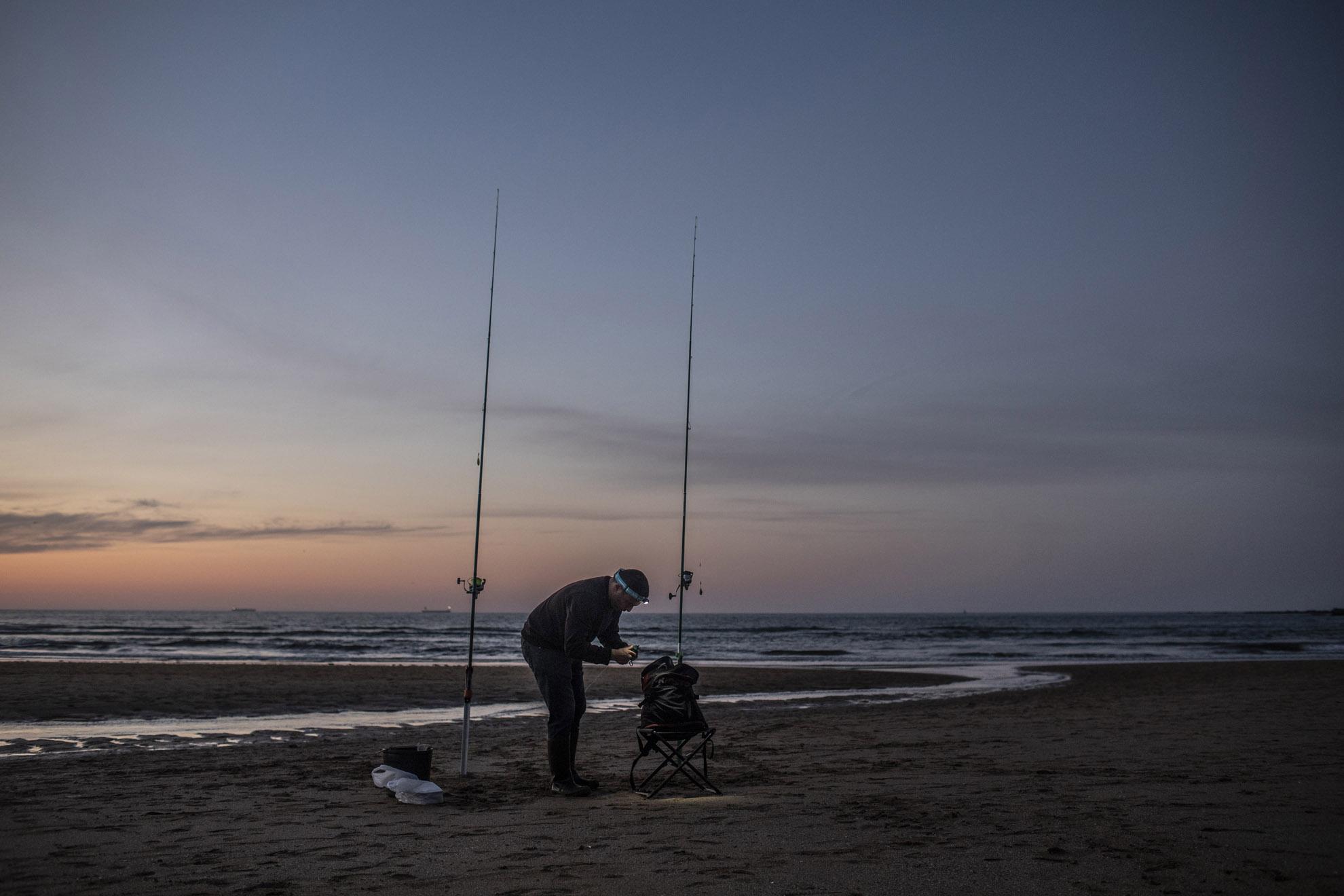 Un pescador prepara su equipo para un día de pesca en la playa de San Lorenzo en Gijón, Asturias, España, 25 de mayo de 2020.