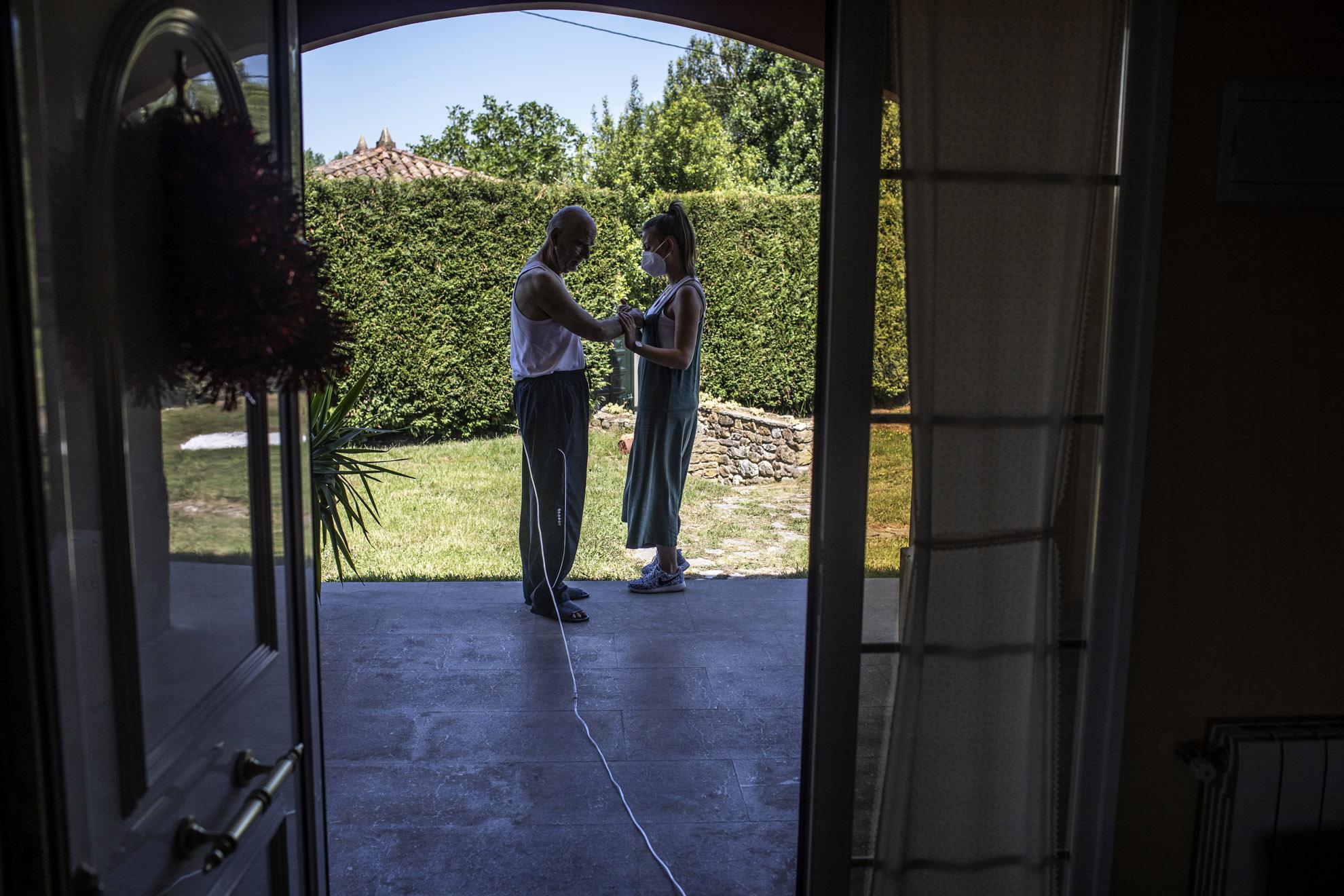 """El Dr. Yahia Zanabili, 69, es Medico jubilado del Servicio de Salud Público de Asturias e ingresó en la UCI del HUCA (Hospital Universitario central de Asturias) a mediados de Marzo por Coronavirus. Su diagnostico era grave y, en sus propias palabras, """"la ha visto muy cerca"""". Aún así, Yahia ha sido doblemente afortunado. Primero por sobrevivir a una enfermedad que en los últimos meses se ha llevado la vida de 28000 personas en España. Segundo por poder recibir las visitas de su hija Layla y su hijo Amr, ambos doctores en el HUCA. En estas semanas ha habido recaídas, un marcapasos, unos pulmones reventados y una rehabilitación muy lenta y muy dura. En la imagen, El Dr. Zanabili, durante un sesión de rehabilitación, consigue alargar su paseo por primera vez hasta el porche de su casa con la ayuda de su fisioterapeuta en Oviedo, Asturias, España. Mayo 2020."""