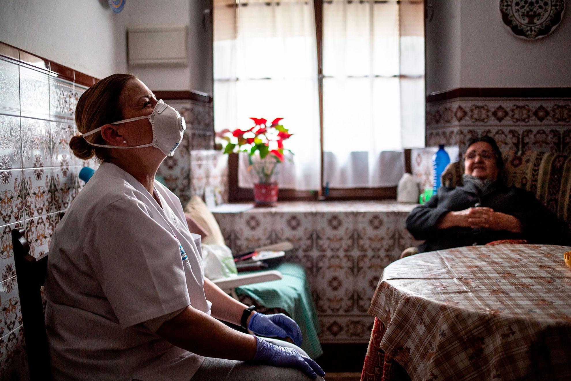 """Mari Carmen trabaja en el servicio de ayuda a domicilio del Ayuntamiento de Aracena (Huelva). Desde que empezó la pandemia del COVID19, sus once usuarios no han pisado la calle. Su llegada a la casas de ancianos a los que atiende, supone para muchos, el mejor momento del día, más allá, la única conversación del día. Lo de menos es que ayude a los mayores en sus tareas domésticas o de aseo personal. Lo de más, ese rato de chascarrillos, de risas, de recuerdos, de compañía al fin y al cabo. Hoy visita a la alegre Luisa, de 75 años. Le ayuda en las tareas de aseo, le trae las medicinas de la farmacia, la compra, deja el suelo brillante... y sobre todo rien juntas a carcajadas. Luisa intenta dar conversación a Mari Carmen para estirar su visita un poco mas: """"¿Quieres un zumito? dice. Pero Maruja de 80 años, ya espera impaciente la llegada de este ángel que viste de blanco."""