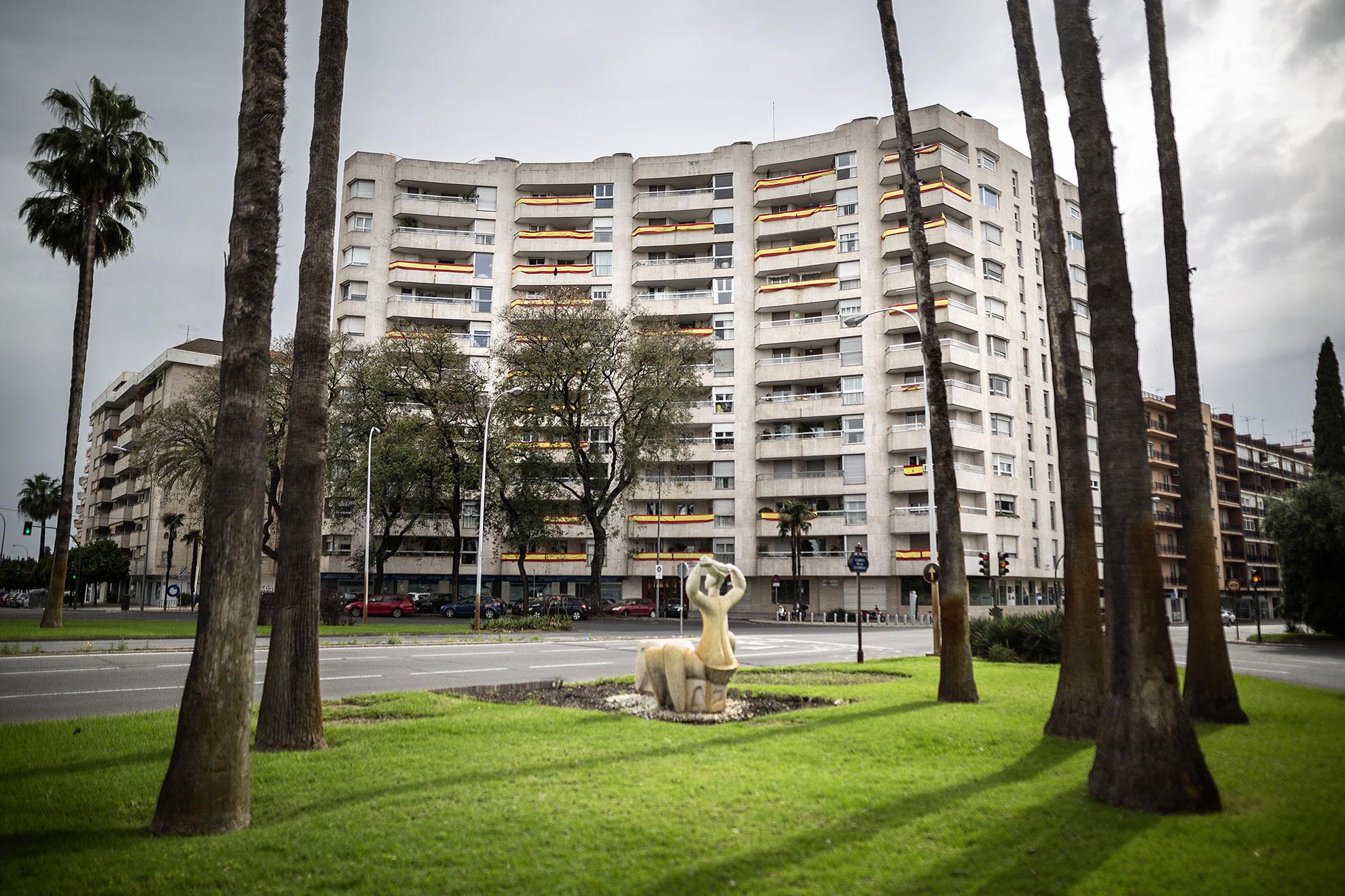 En pleno barrio de los Remedios, La Glorieta de las Cigarreras en Sevilla luce vacía en pleno confinamiento por el COVID19. Empiezan a llenarse, por toda la ciudad, balcones y ventanas ataviados con banderas de España portando crespones negros en señal de duelo por las personas fallecidas a causa del coronavirus. A día 25 de Abril, según datos facilitados por el Gobierno de España, al menos 22.902 personas han perdido la vida a causa de la pandemia en España.