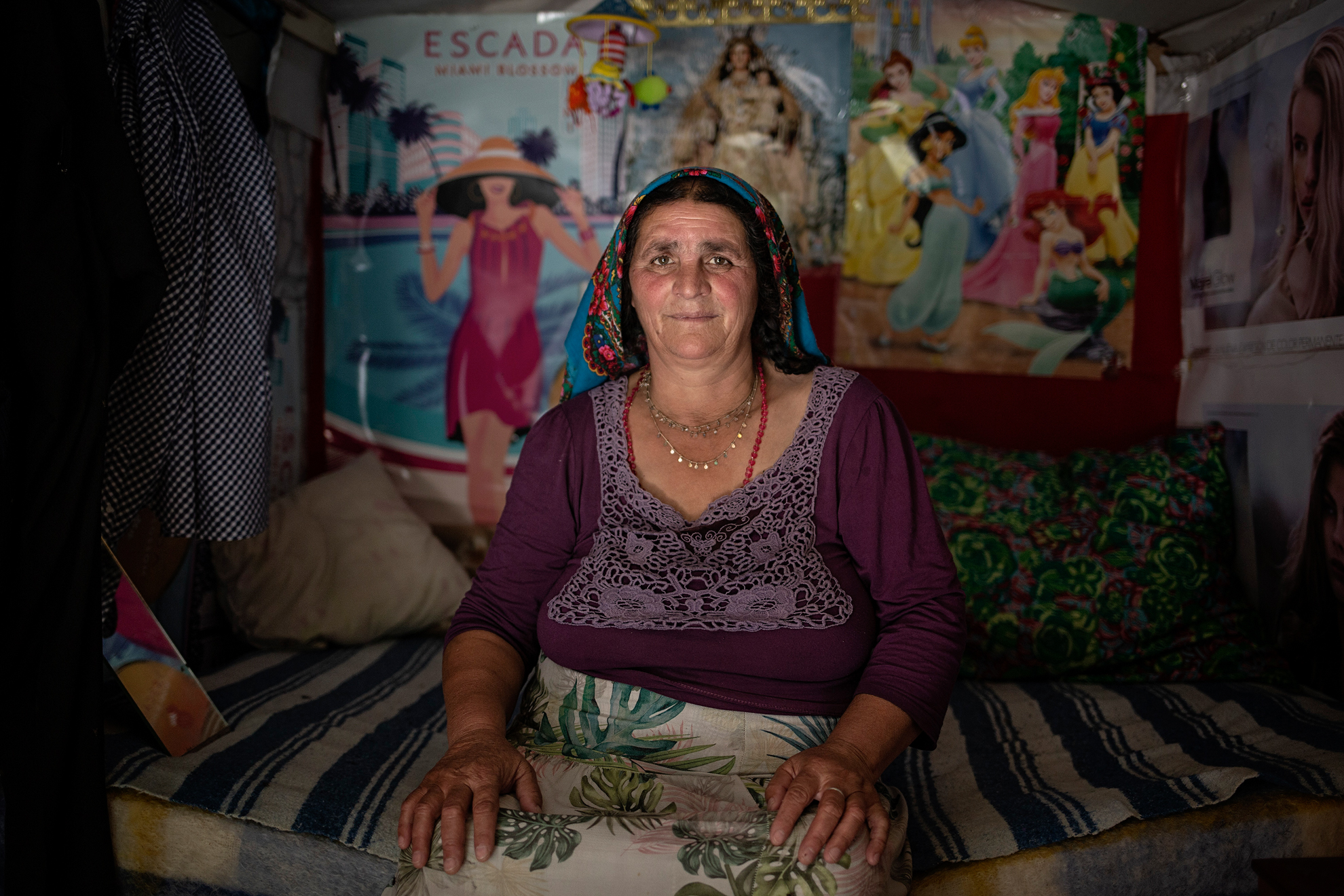 """on casi las 3 de la tarde y Marichica se protege del calor sentada en la cama de su dormitorio. No sorprende tanto la humildad de la chabola, como el exquisito orden, la limpieza y sobre todo, los posters que decoran las paredes: """"Es mi casa"""" dice orgullosa del diminuto habitáculo, en un español muy básico. Lleva 6 años viviendo en el asentamiento chabolista de familias rumanas a orillas del río Guadalquivir. Vinieron buscando trabajo y oportunidades para sostener la familia que quedaba en Rumanía, pero desde que se decretó la alera sanitaria por el COVID19 se han quedado sin ingresos. Son más de 20 personas que están viviendo estas semanas exclusivamente de los alimentos que les entregan a diario organizaciones como Médicos del Mundo. Toda la comida que reciben y consiguen la comparten y cocinan en comunidad. Y en ese español básico una y otra vez, la misma palabra: """"gracias, gracias, gracias""""."""